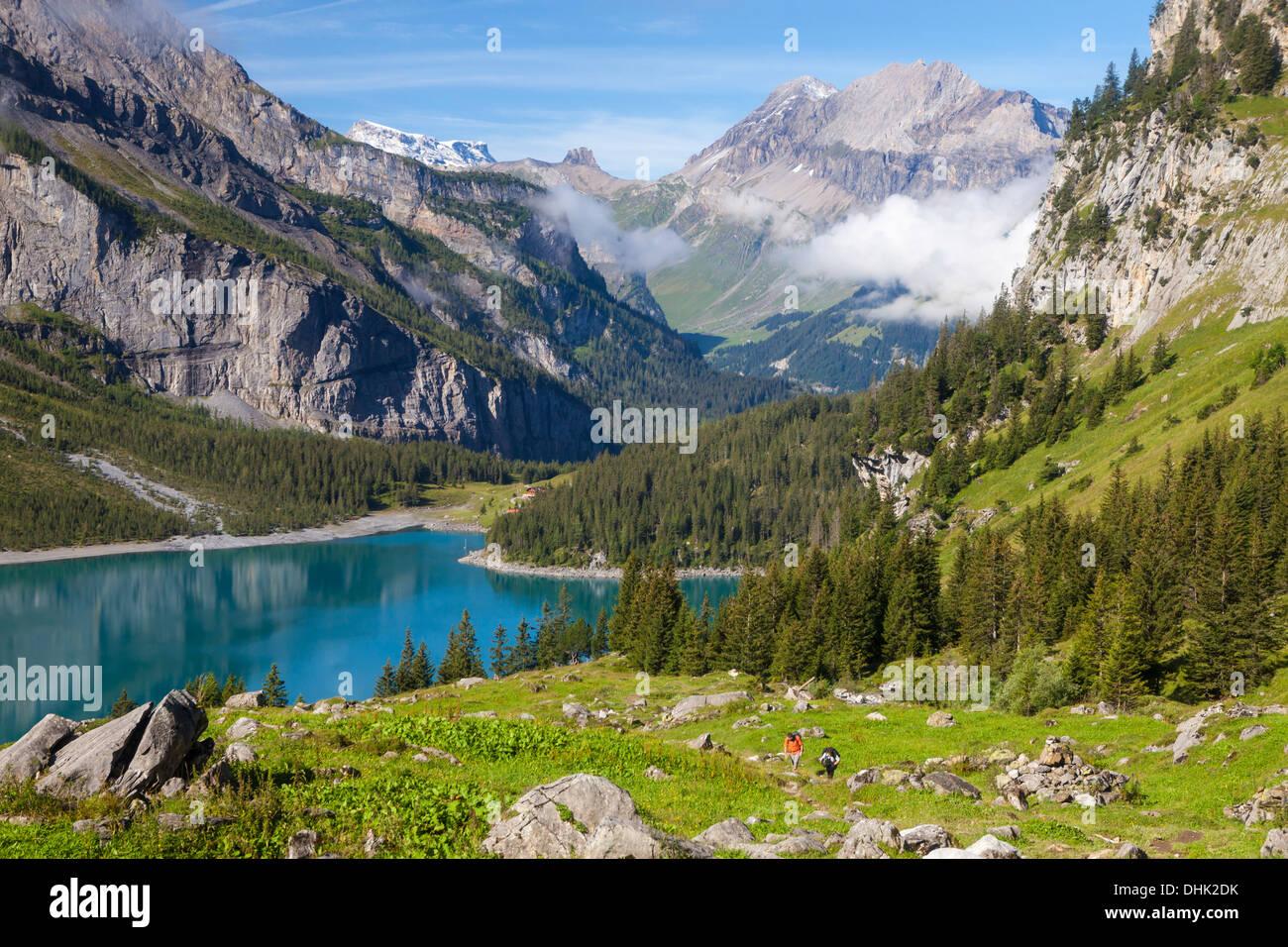 Un uomo e una donna escursionismo sopra il lago di Oeschinen, Alp Unterbaergli, vista del Wildstrubel, Oberland Foto Stock