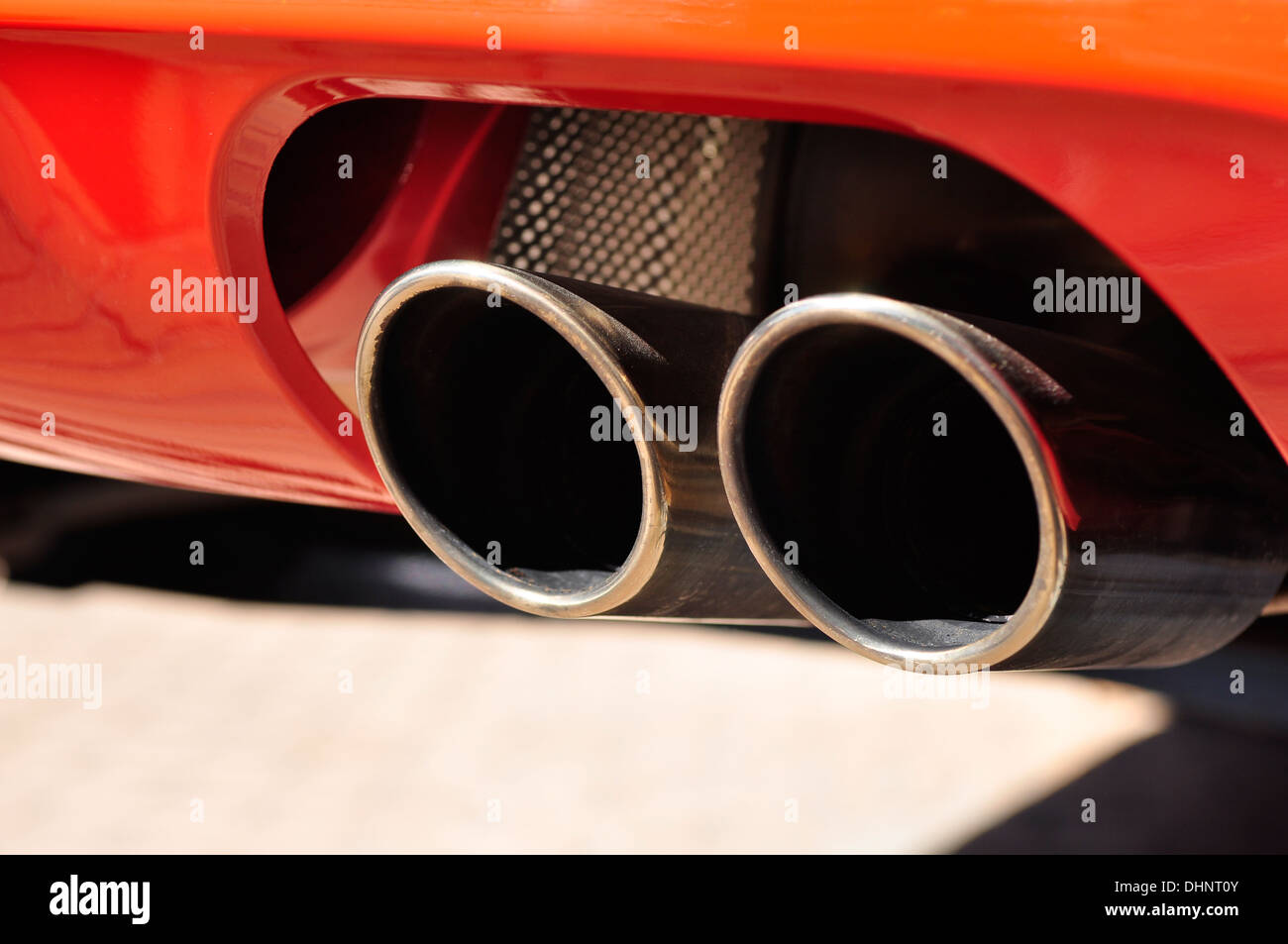 Close up di un automobile rossa doppia tubazione di scarico Immagini Stock