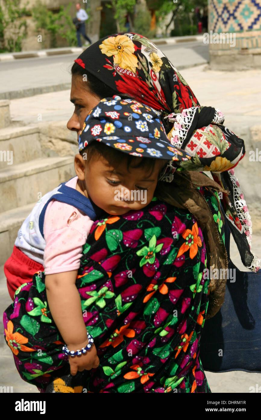 Uzbek Lady in Uzbekistan trasporta un bambino piccolo. Ella è indossando il tradizionale khan atlas Abito tunica con motivi ricamati. Immagini Stock