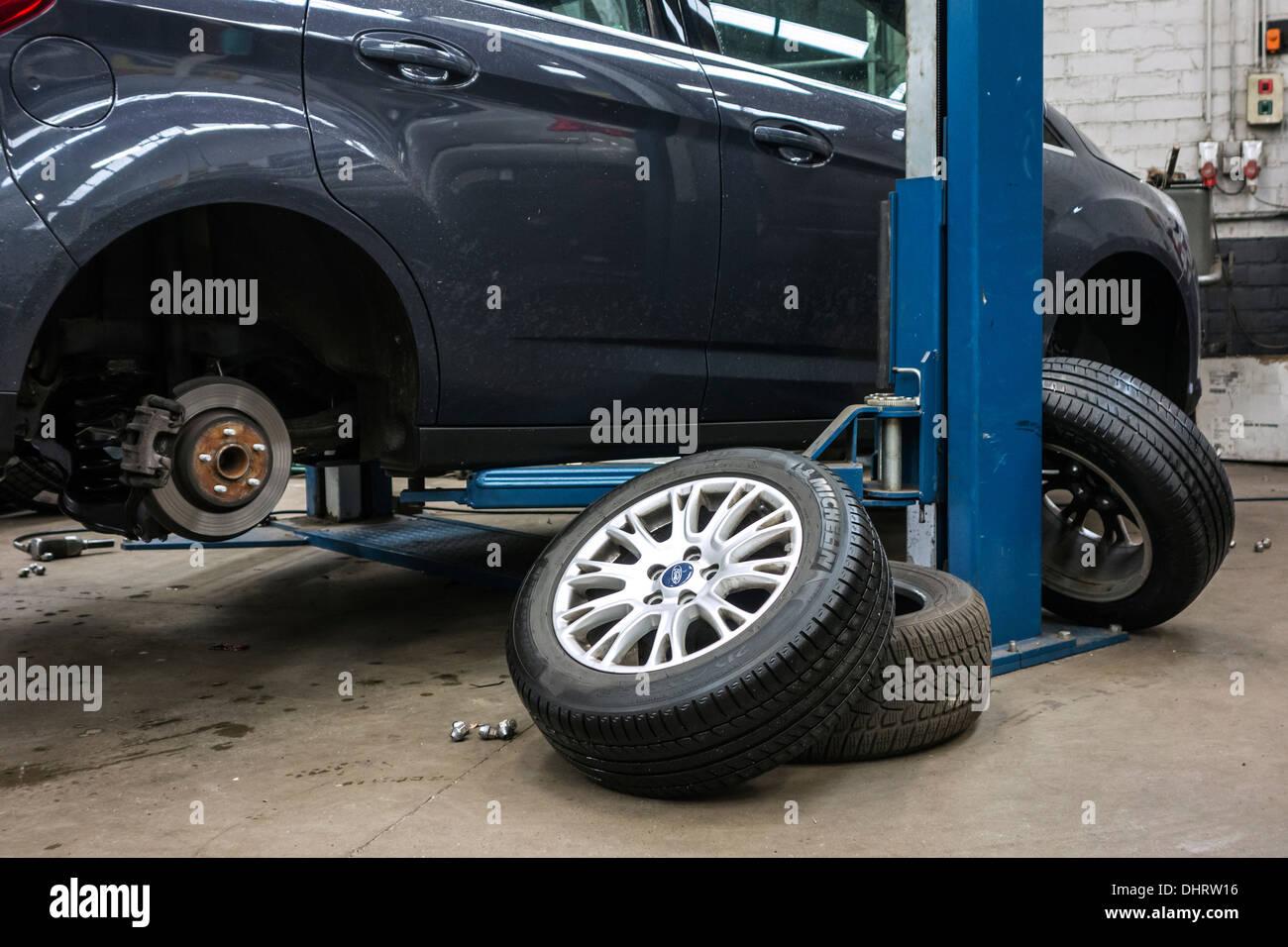 Modifica di pneumatici estivi e invernali di montaggio pneumatici sulle ruote delle auto sulla rampa in officina di assemblaggio del centro del pneumatico Immagini Stock