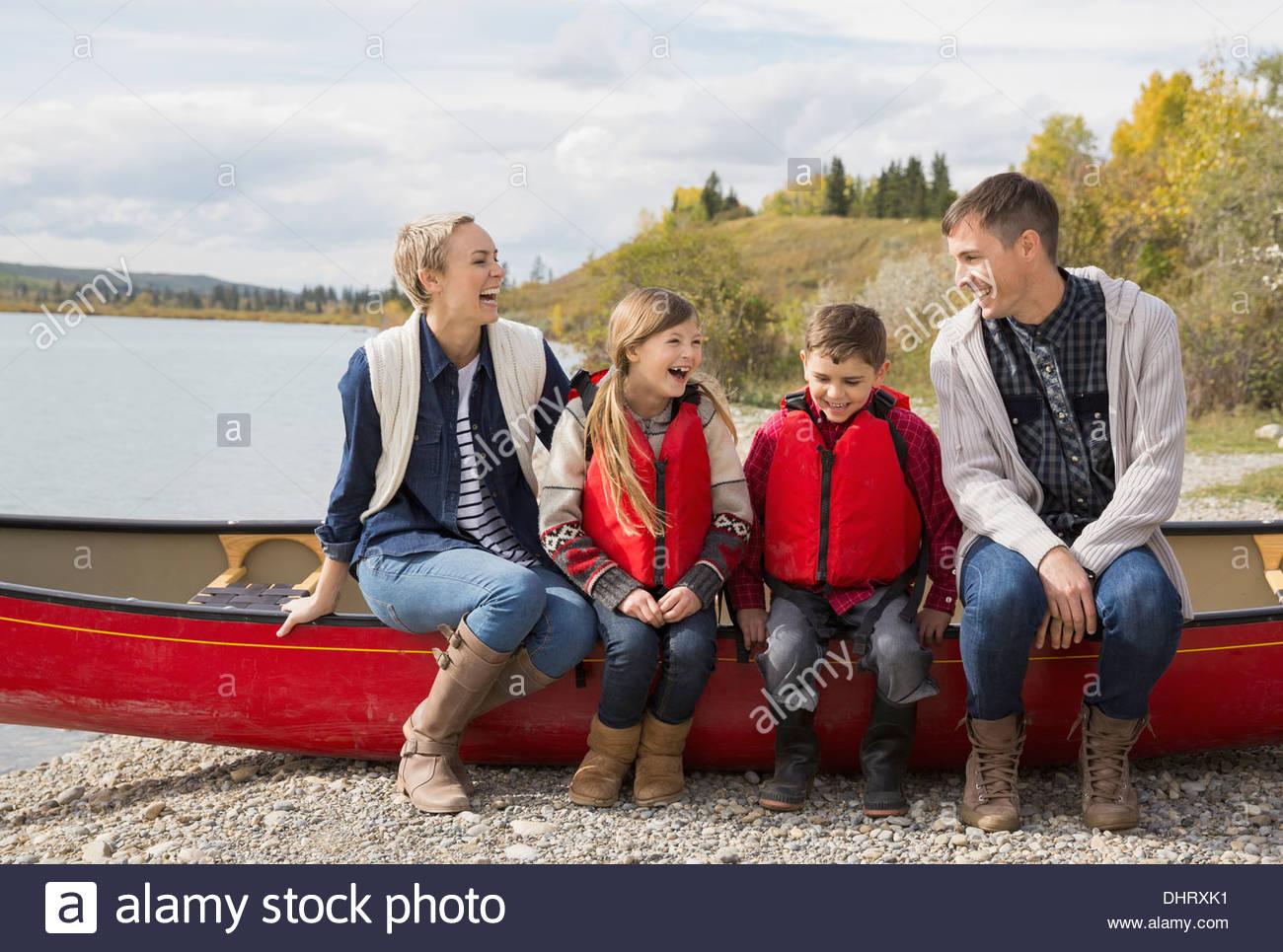 La famiglia felice seduti insieme in canoa sul lungolago Immagini Stock