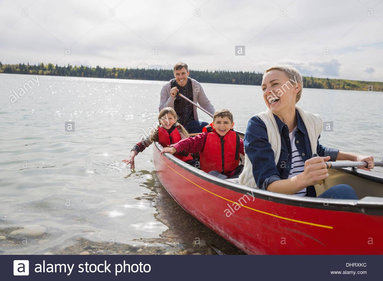 La famiglia felice in canoa sul lago Immagini Stock