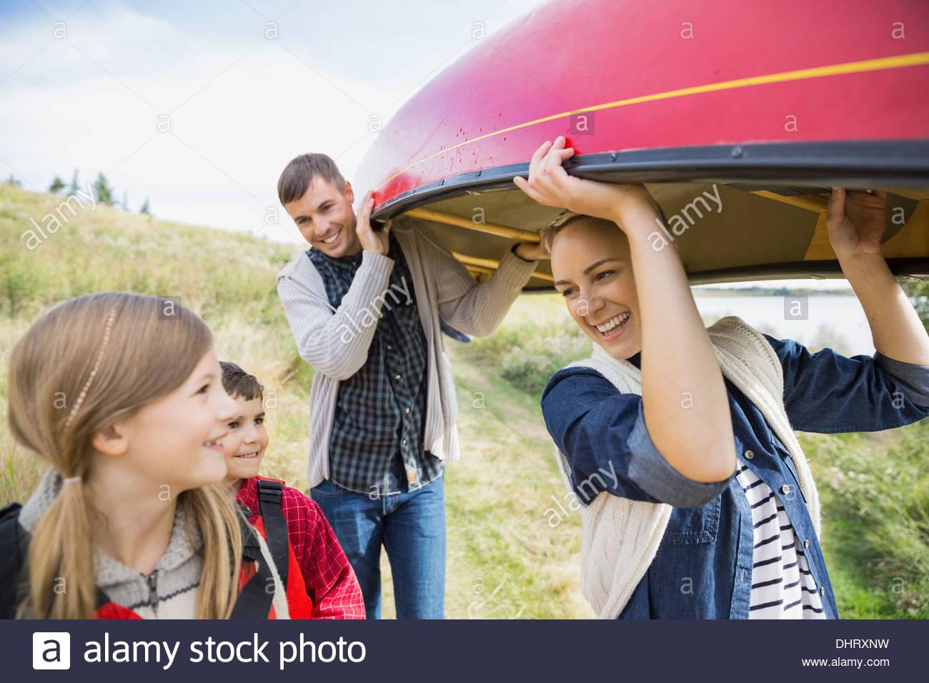 Famiglia portando canoe a lakeshore Immagini Stock