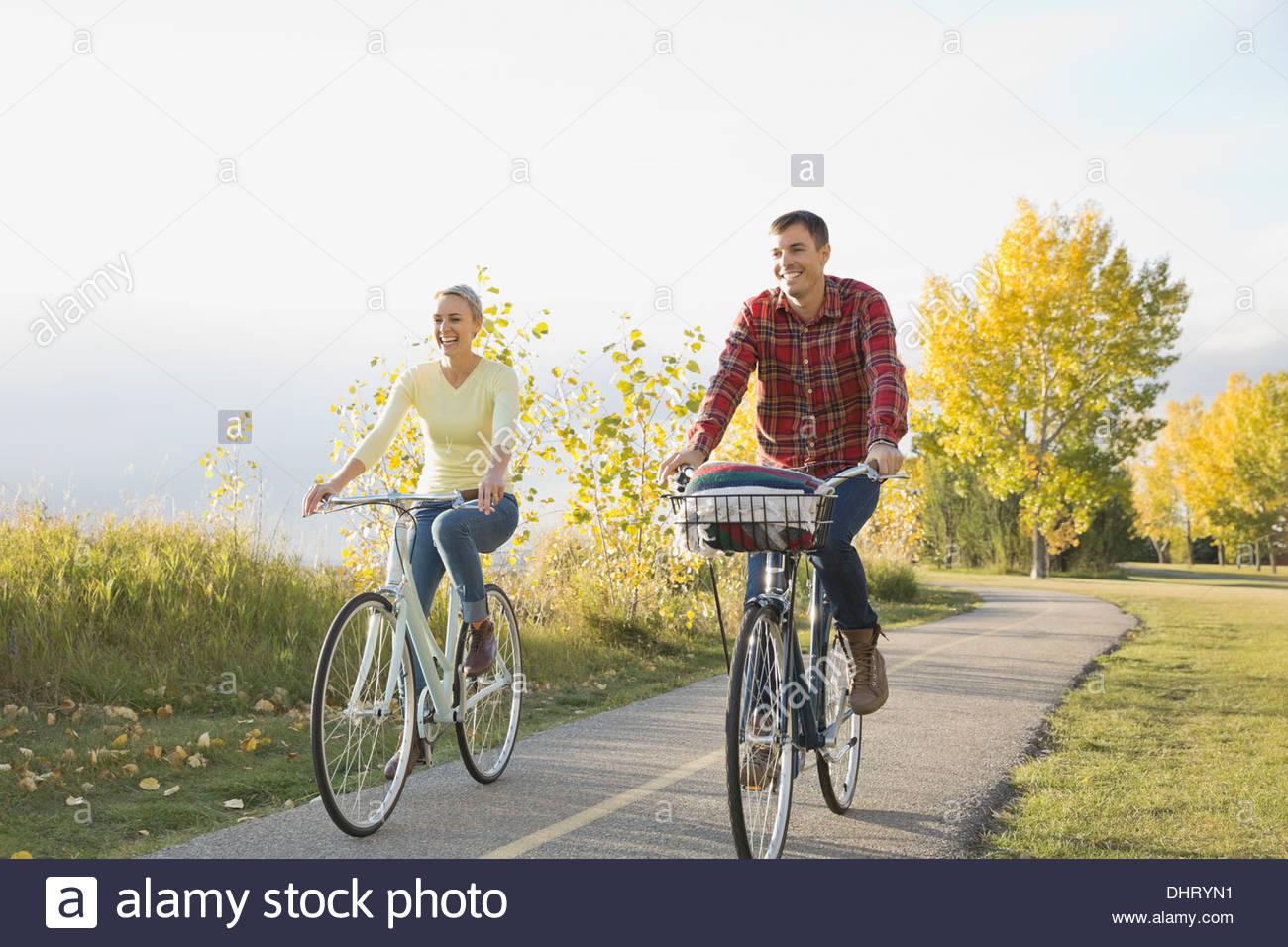 Coppia felice ciclismo su strada di campagna Immagini Stock