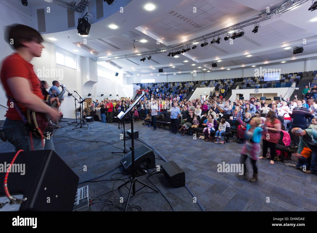 Congregazione che partecipano al culto contemporaneo la musica durante il servizio domenicale all'interno del grande Re moderna Chiesa della comunità. Immagini Stock