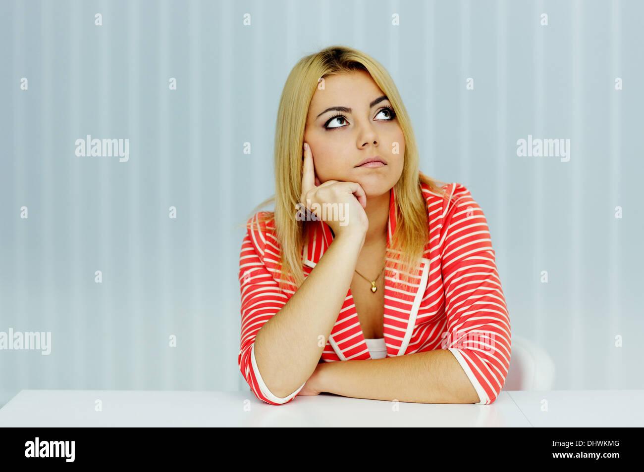 Giovane donna pensosa in giacca rossa seduta al tavolo in ufficio Immagini Stock