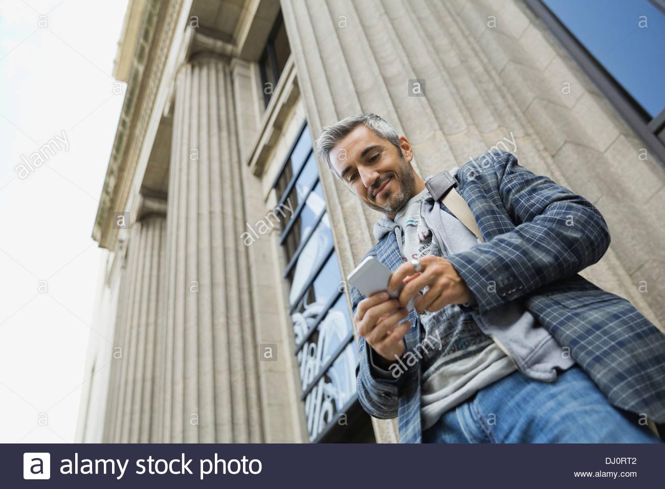 Basso angolo di visione dell'uomo utilizzando smart phone all'aperto Immagini Stock