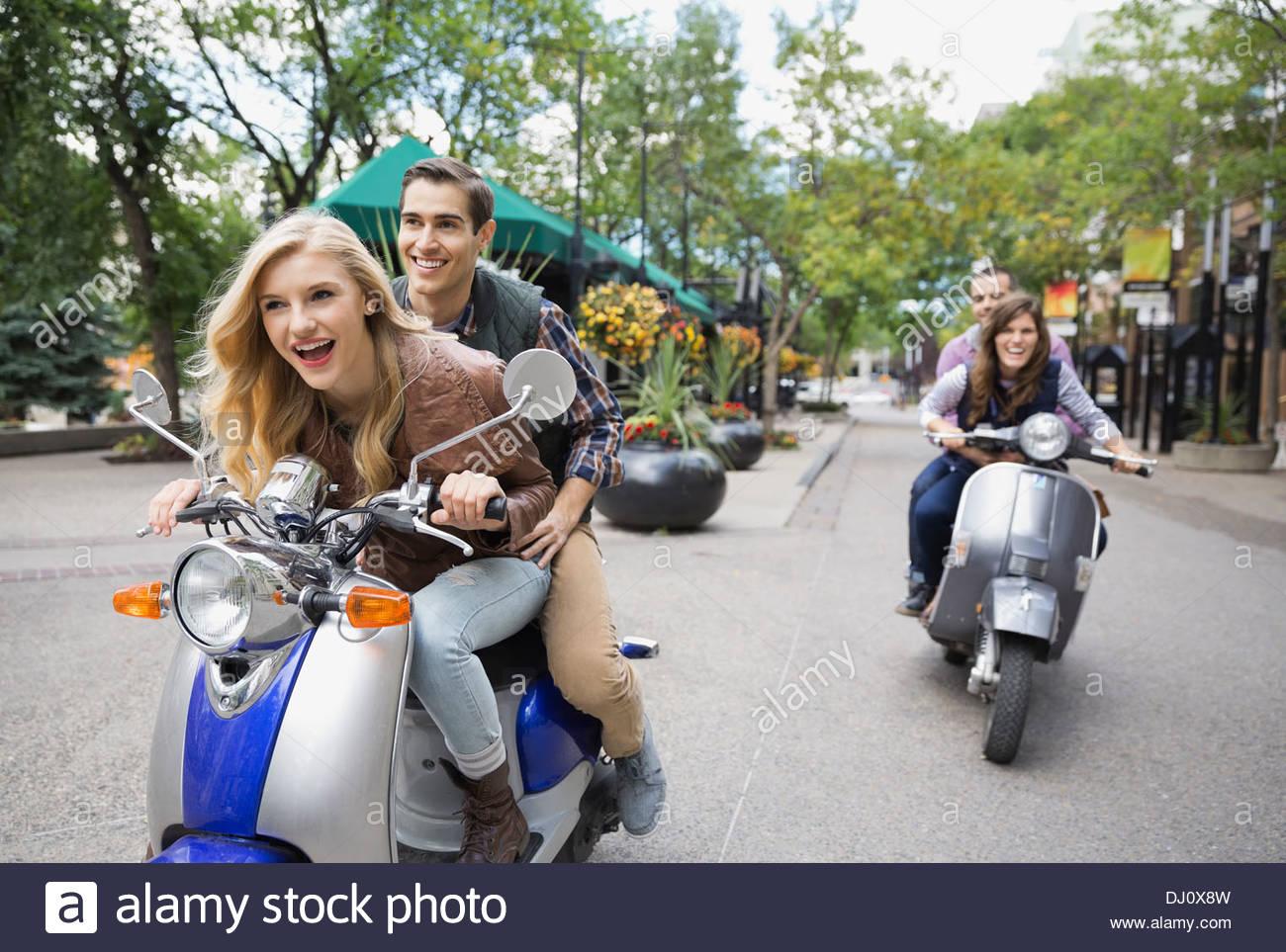 Due coppie in sella scooter sulla strada di città Immagini Stock