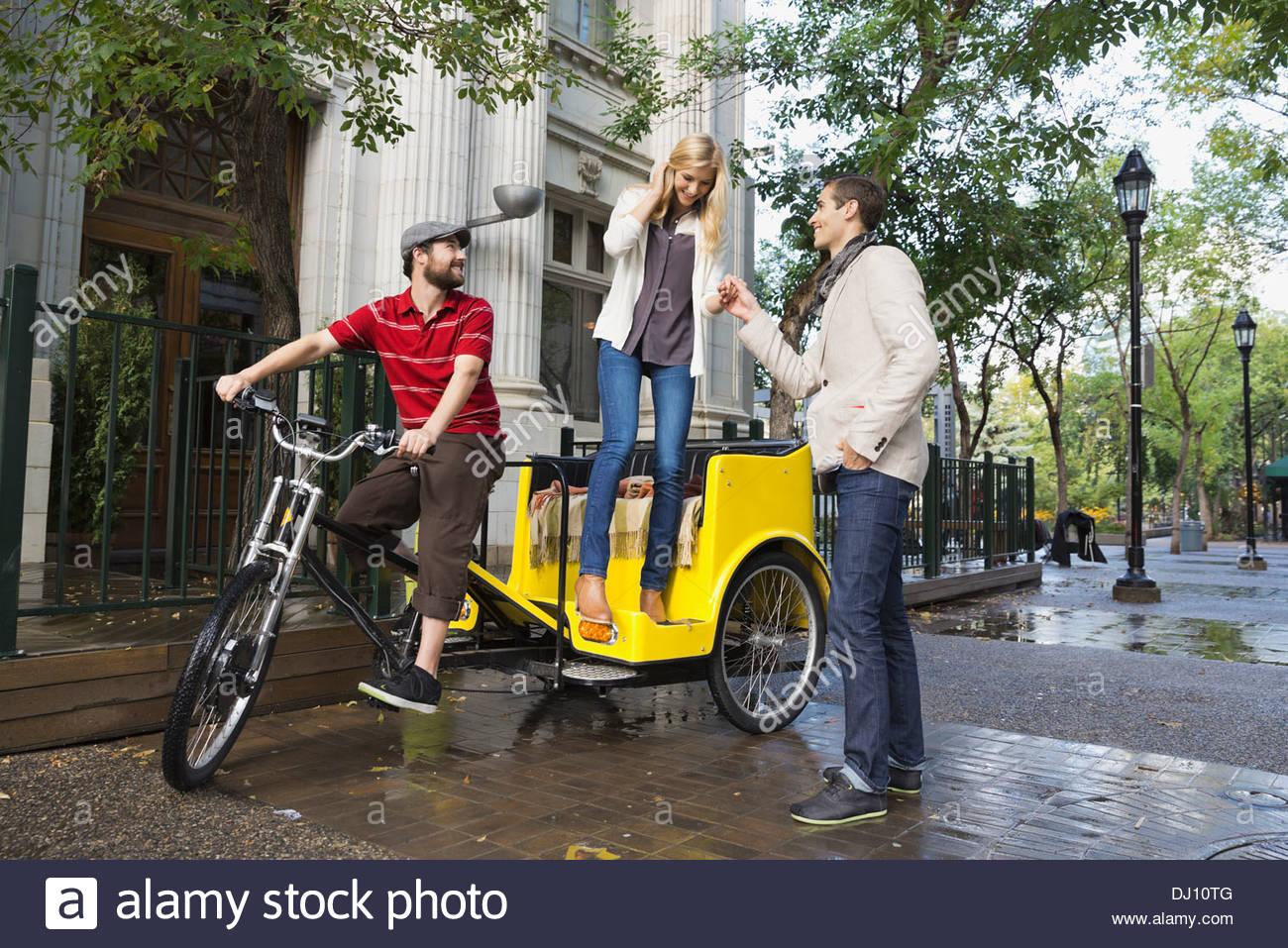 Uomo Donna assistenza al di fuori del rickshaw Immagini Stock