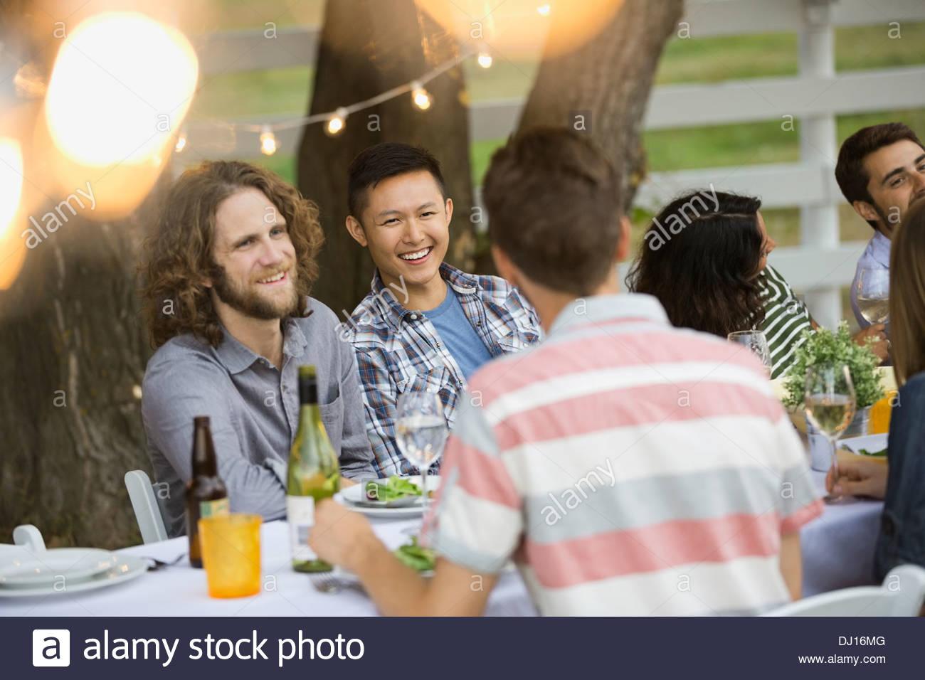 Multietnica amici godendo outdoor dinner party Immagini Stock