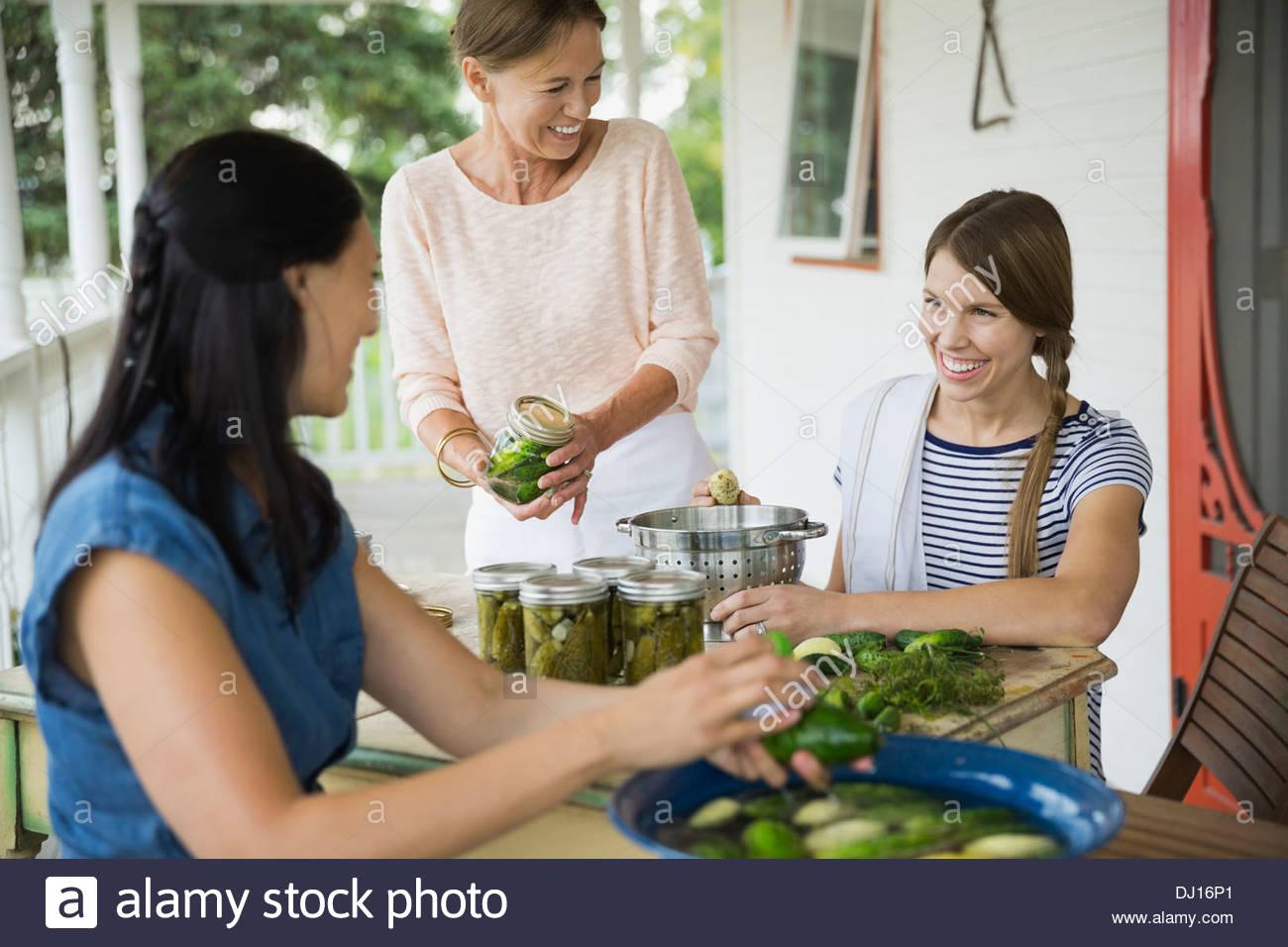 Femmina ai membri della famiglia la preparazione di ortaggi può Immagini Stock