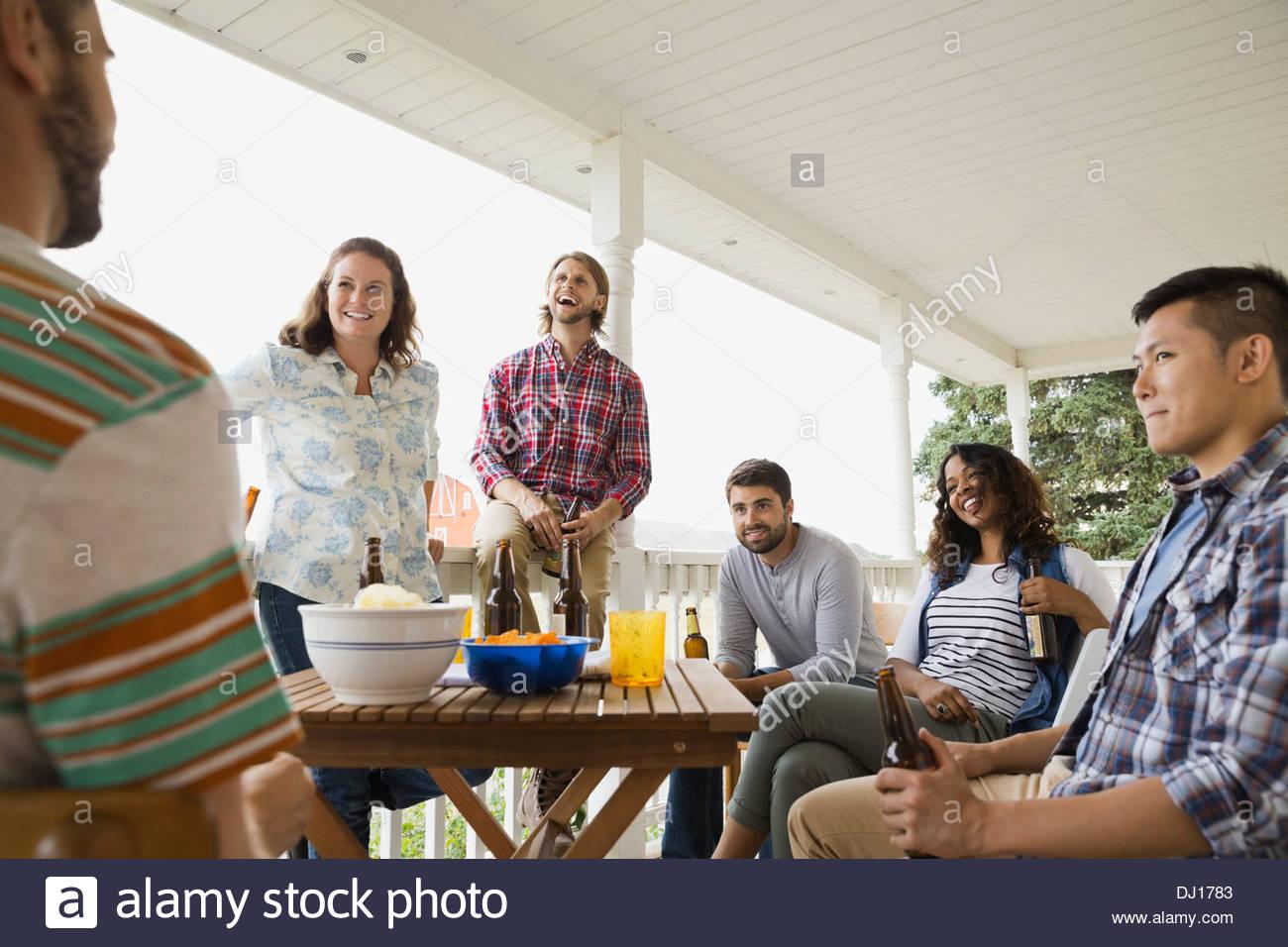 Multietnica gli amici sorseggiando un drink sul portico Immagini Stock