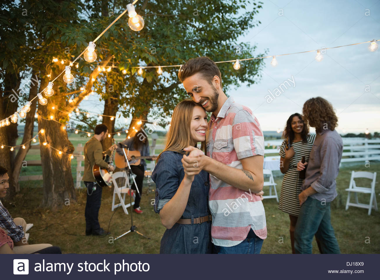 Felice coppia giovane dancing at outdoor farm party Immagini Stock