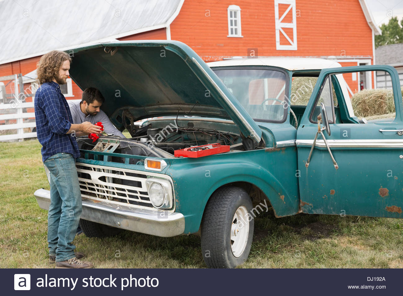 Gli uomini la riparazione pickup truck in agriturismo Immagini Stock