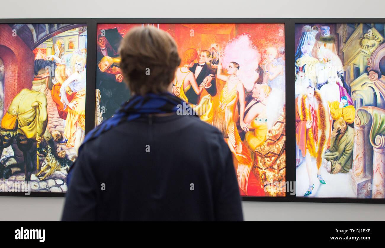 """Mannheim, Germania. Xviii Nov, 2013. Una donna che sta di fronte alla riproduzione delle opere d'arte 'Grossstadt' (metropoli) da Otto Dix nella mostra """"ix/Beckmann: Mythos Welt"""" (lit. Dix/Beckmann: Mito Mondo') nella Kunsthalle di Mannheim, Germania, 18 novembre 2013. La mostra sarà aperta il 22 novembre 2013. Foto: Uwe Anspach/dpa/Alamy Live News Immagini Stock"""