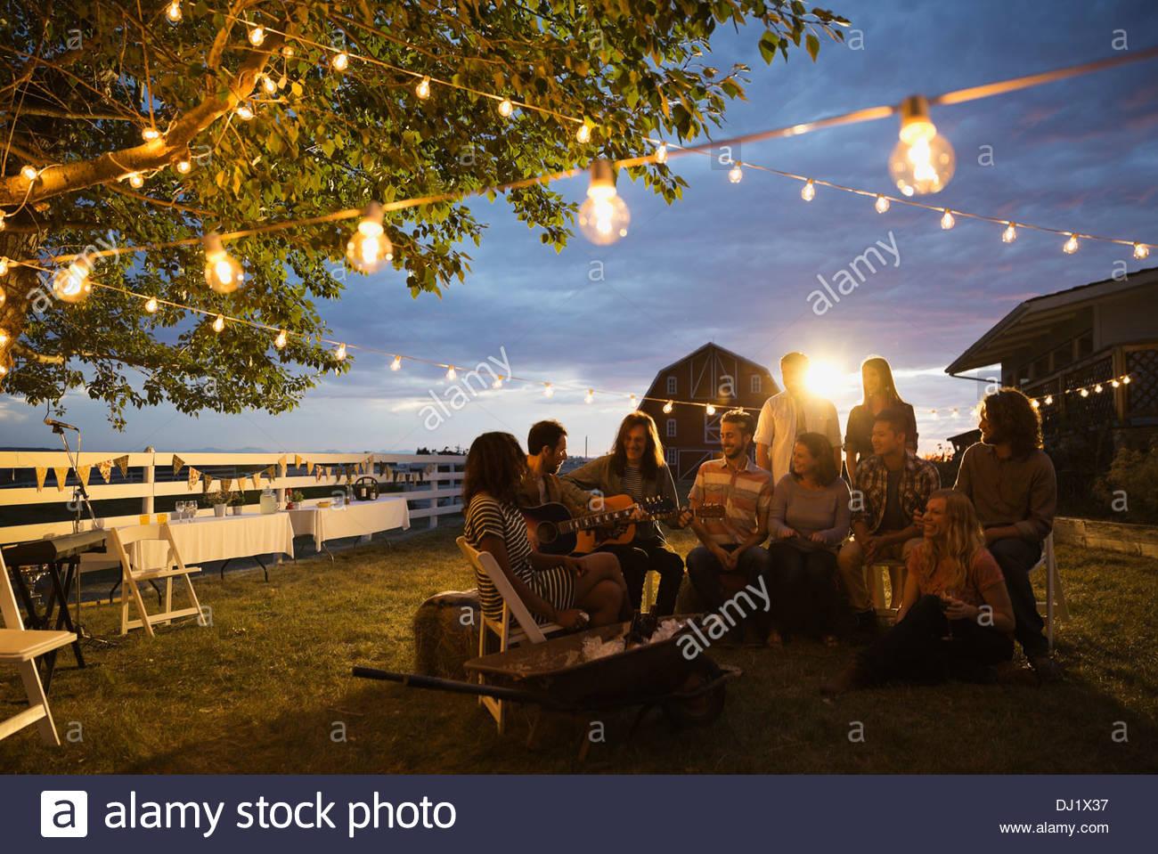 Gruppo di amici multietnico ascoltando chitarristi durante il party al tramonto Immagini Stock