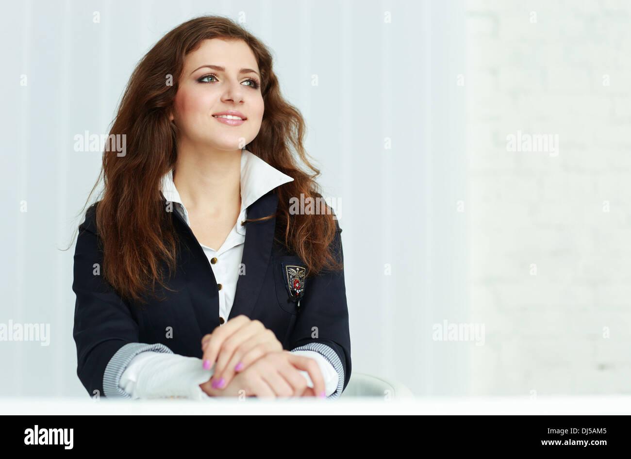 Felice giovane imprenditrice seduta al tavolo e guardando copyspace in office Immagini Stock