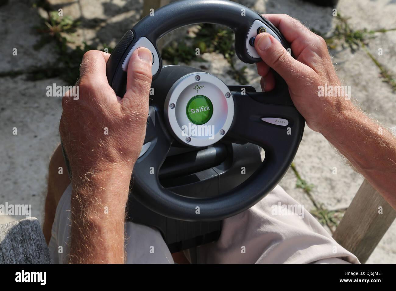 Uomo con Saitek Volante per Xbox console di gioco Immagini Stock