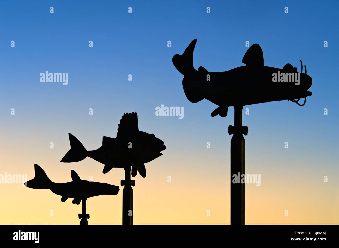Tre sculture di pesce Sihouetted contro il tramonto a Waterfront Park a Louisville, Kentucky Immagini Stock