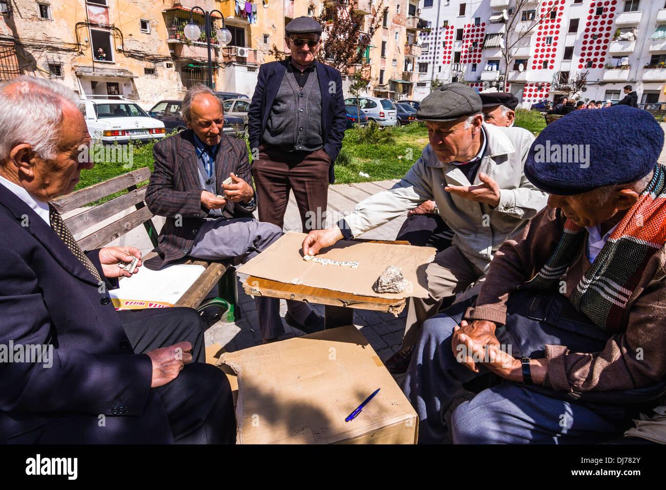Gli uomini anziani gioca domino in strada. Tirana, Albania Immagini Stock