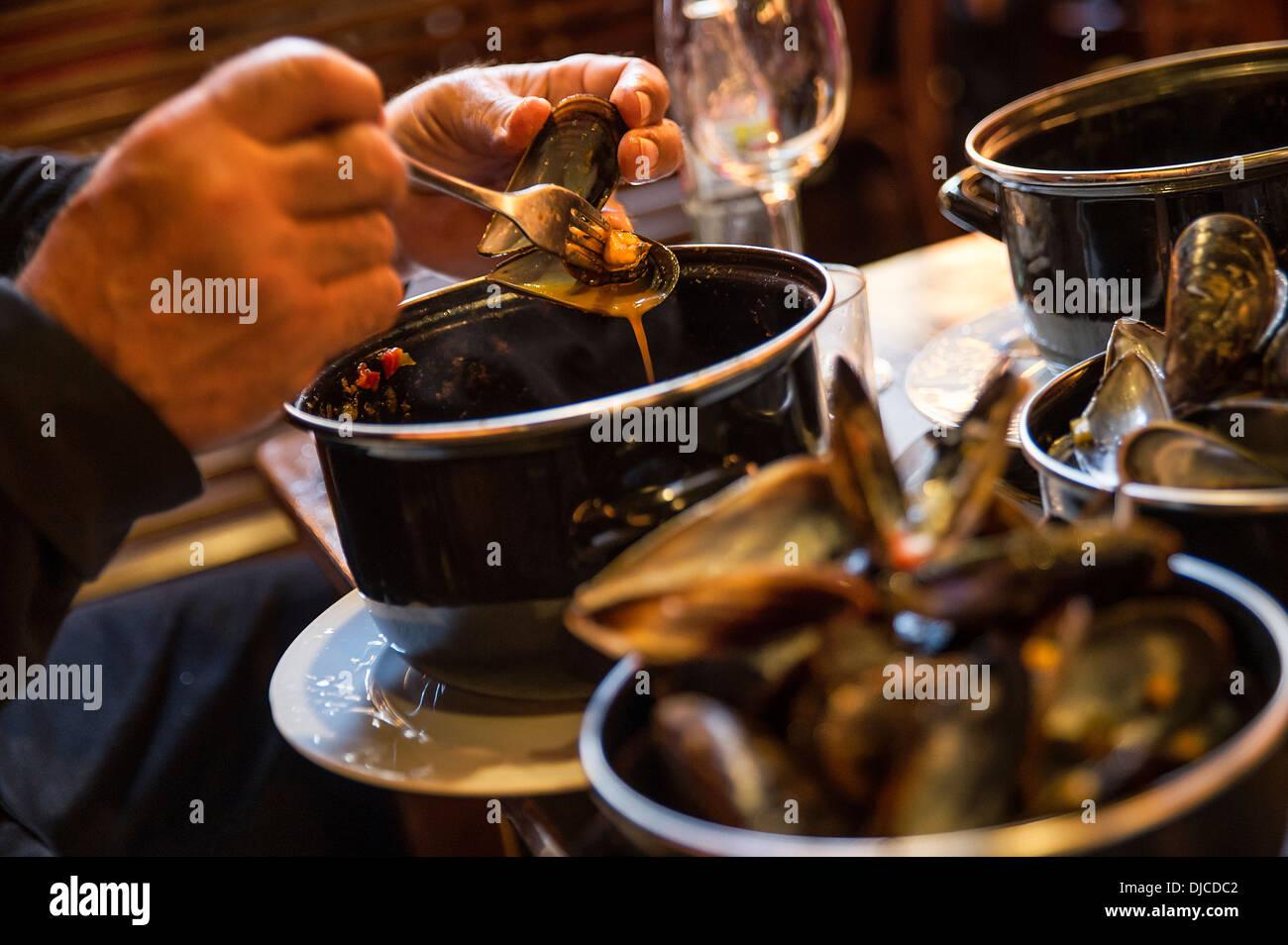 Mecenate gode di un piatto di cozze in un ristorante di tapas, Barcellona, Spagna Immagini Stock
