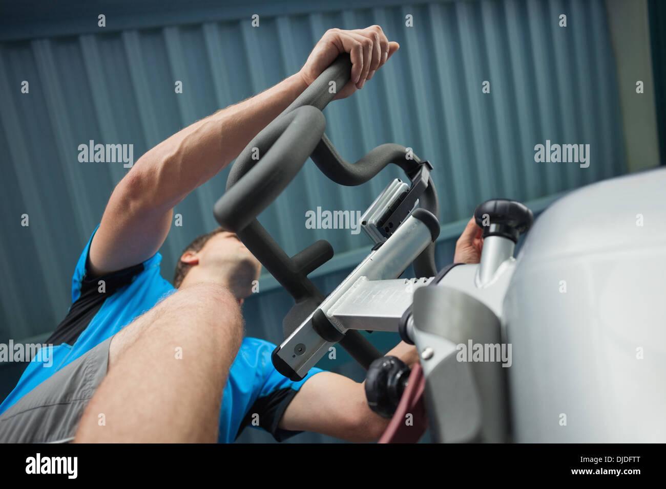 Determinato uomo al lavoro in classe di filatura in palestra Foto Stock
