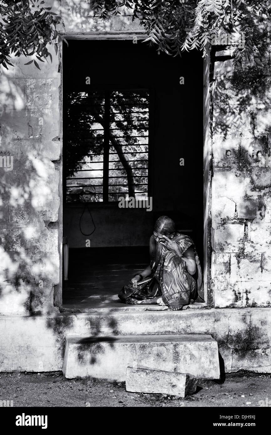 Il vecchio donna indiana sat in una porta al Sri Sathya Sai Baba outreach mobile hospital Clinic. Andhra Pradesh, India. Monocromatico Immagini Stock