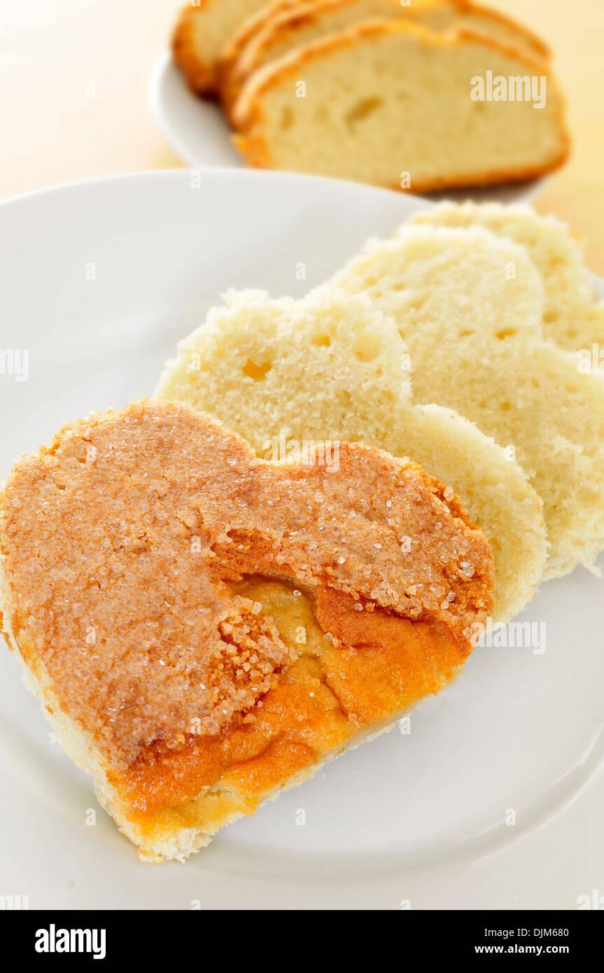Primo piano di alcuni a forma di cuore delle fette di pan di spagna su una piastra Immagini Stock