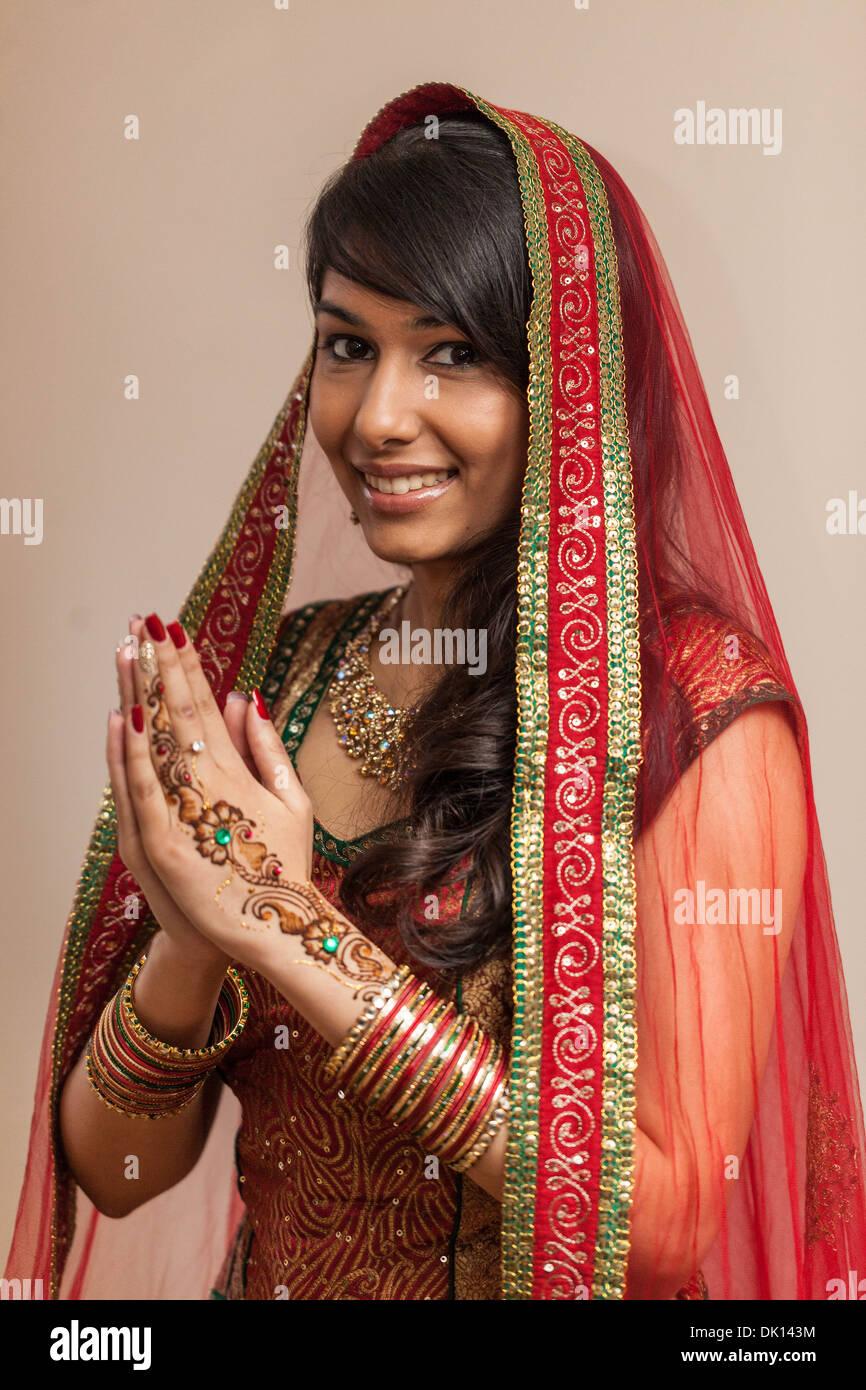 Ritratto di una bellissima donna indiana vestito in abiti tradizionali con Henna Tattoos sulle sue mani, su un Namaste gesto. Immagini Stock