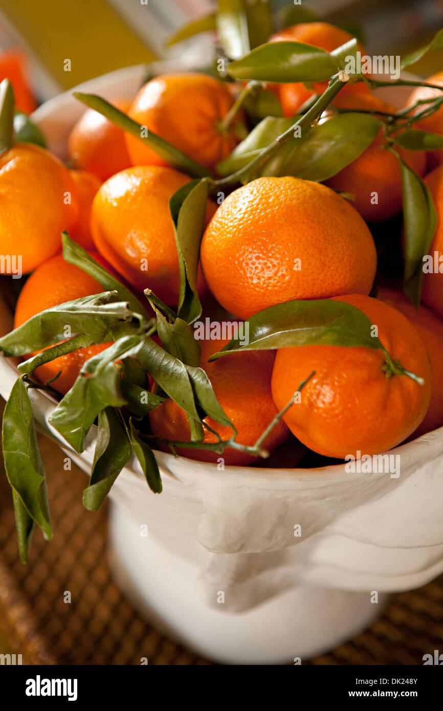 Chiudere fino ad alto angolo di visione delle arance mature tangerini nel recipiente Immagini Stock