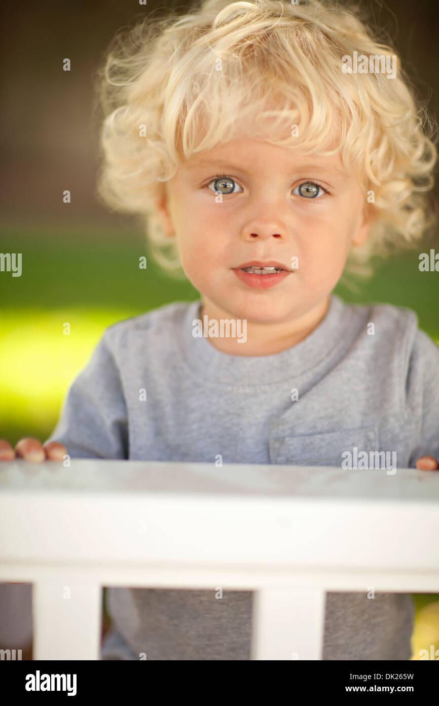 Close up ritratto di bimbo biondo ragazzo con riccioli dietro il recinto Foto Stock