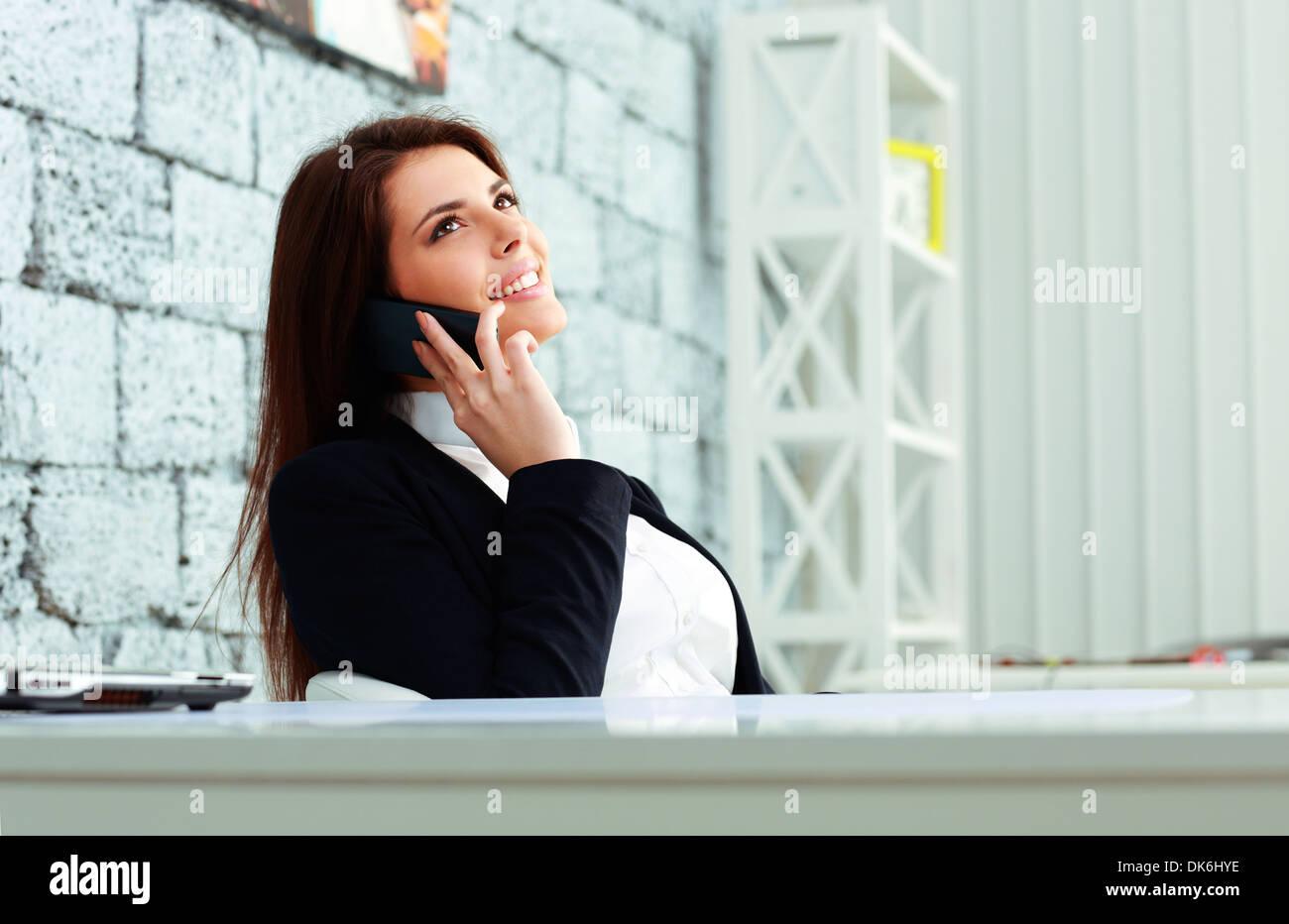 Giovane imprenditrice felice di parlare al telefono e guardando il copyspace in office Immagini Stock