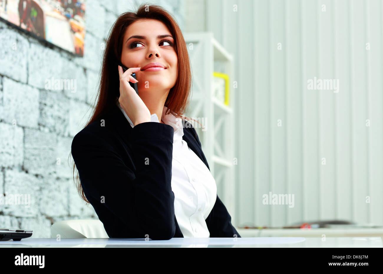 Giovane imprenditrice felice di parlare al telefono e guardando lontano a copyspace in office Immagini Stock
