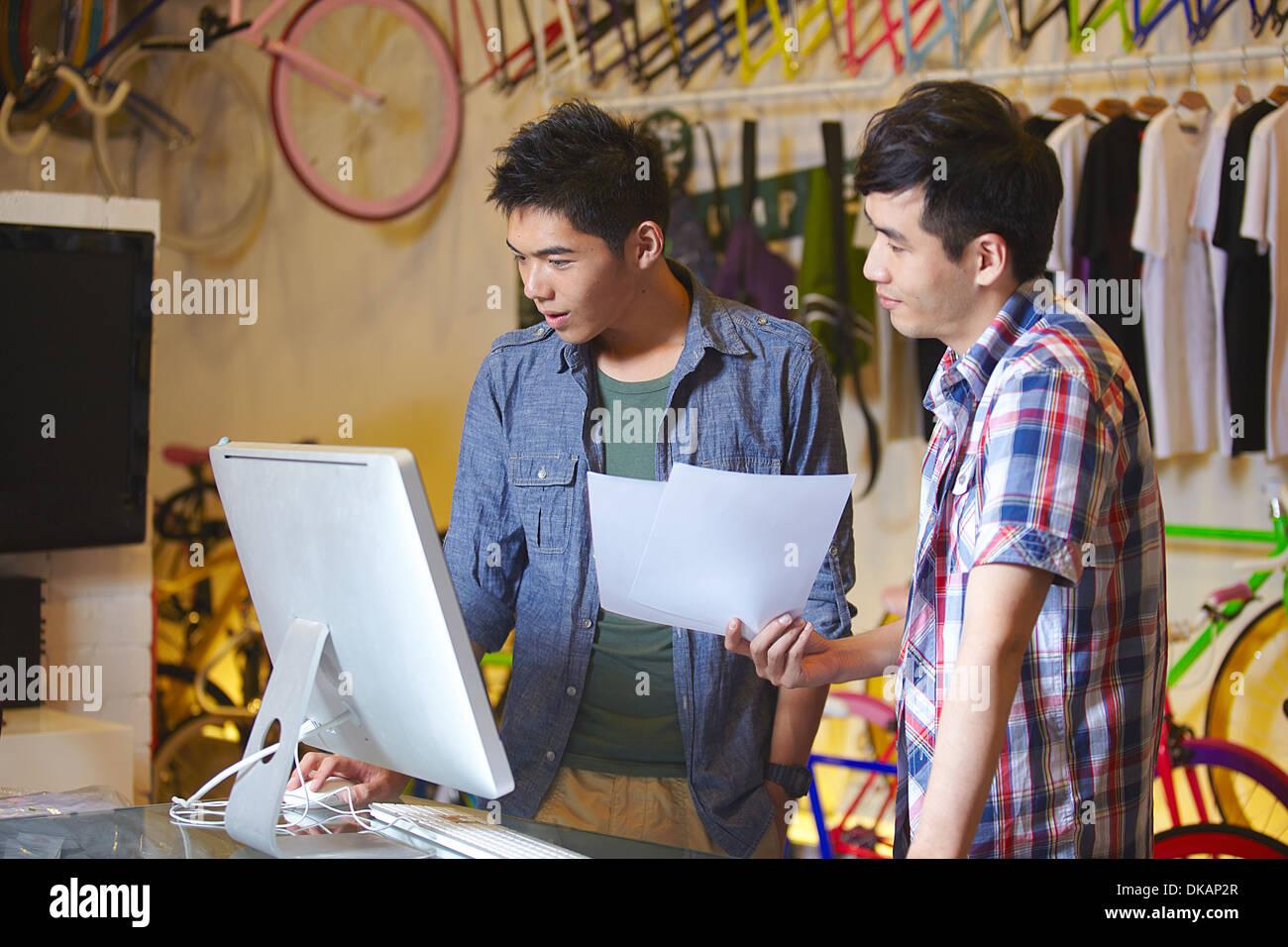 Due giovani uomini in bike shop tramite il computer Immagini Stock