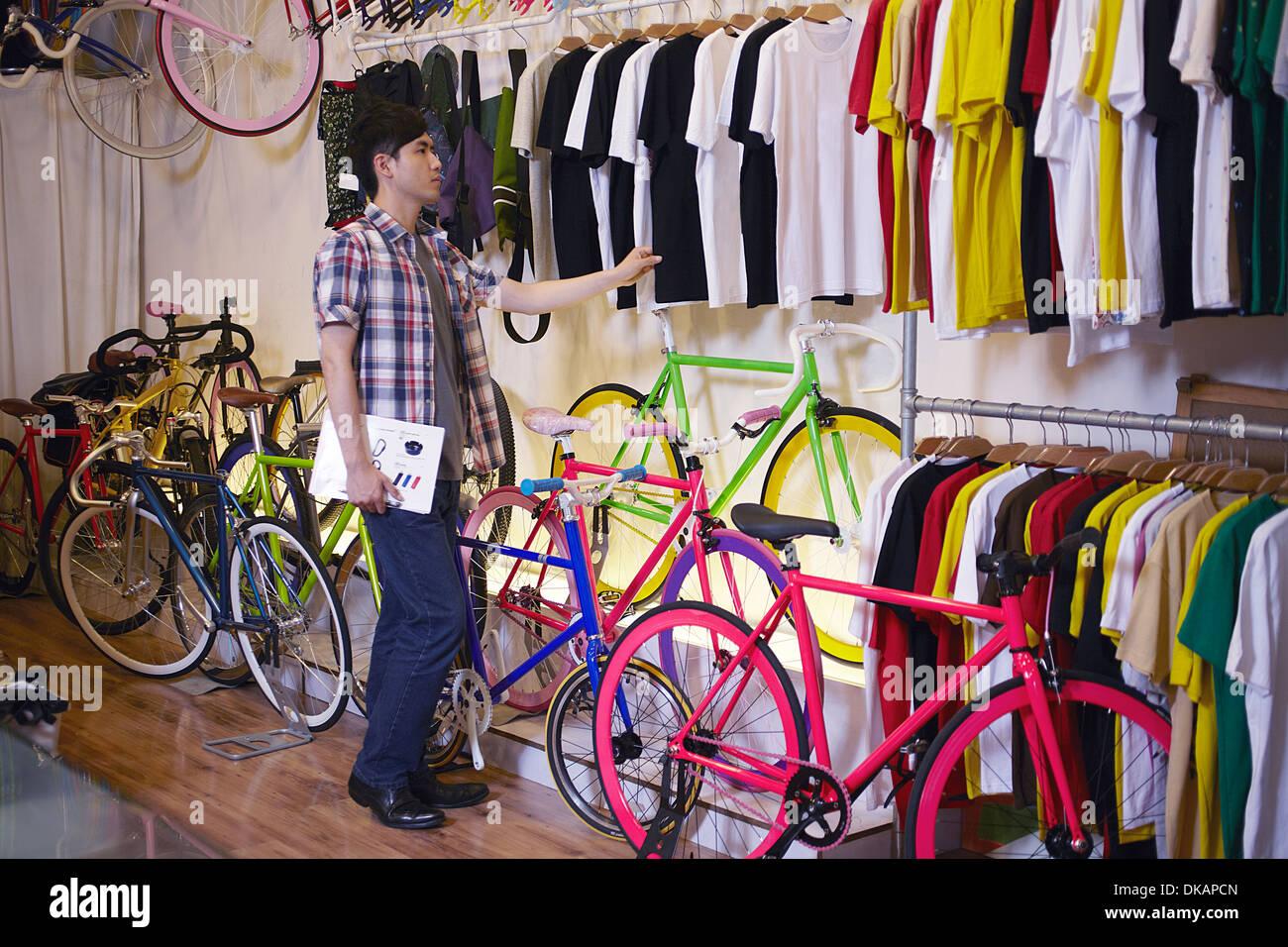 Giovane uomo nel negozio di biciclette scegliendo t shirt Immagini Stock