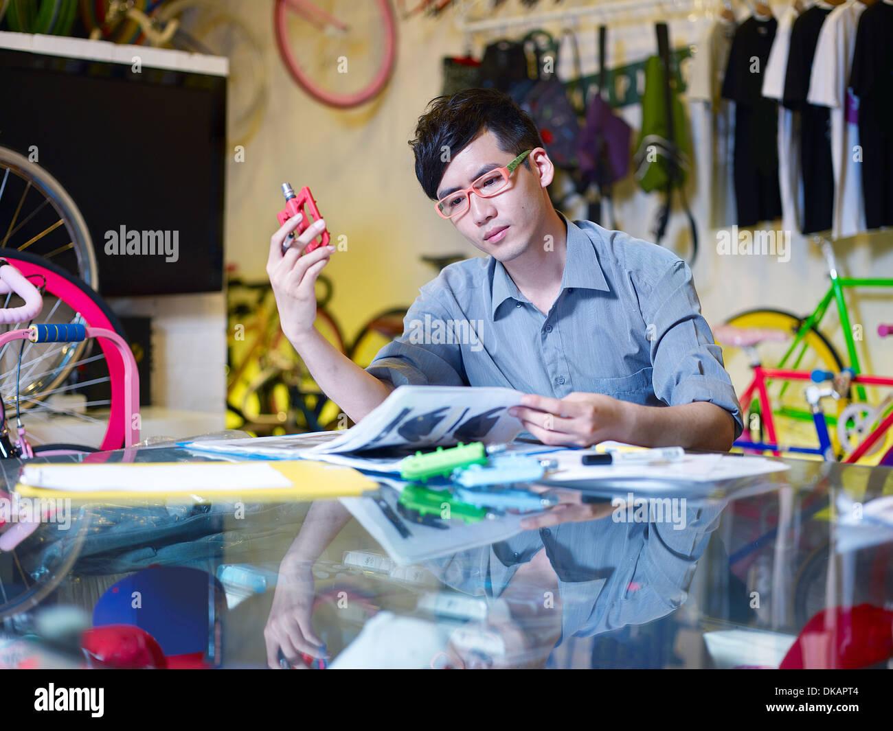 Giovane uomo esaminando parte di bicicletta in bike shop Immagini Stock