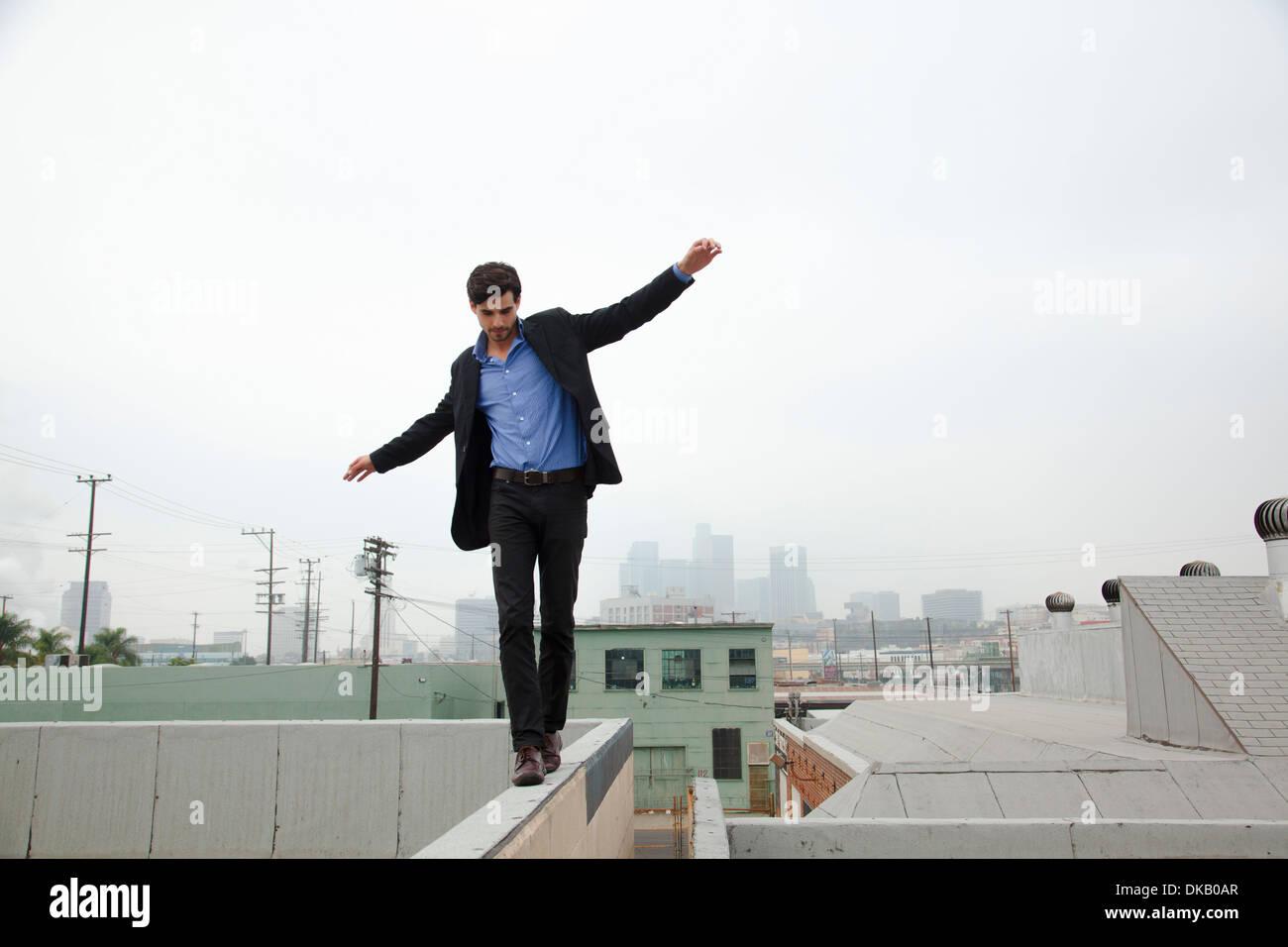 Giovane uomo parete a piedi sul tetto della città Immagini Stock