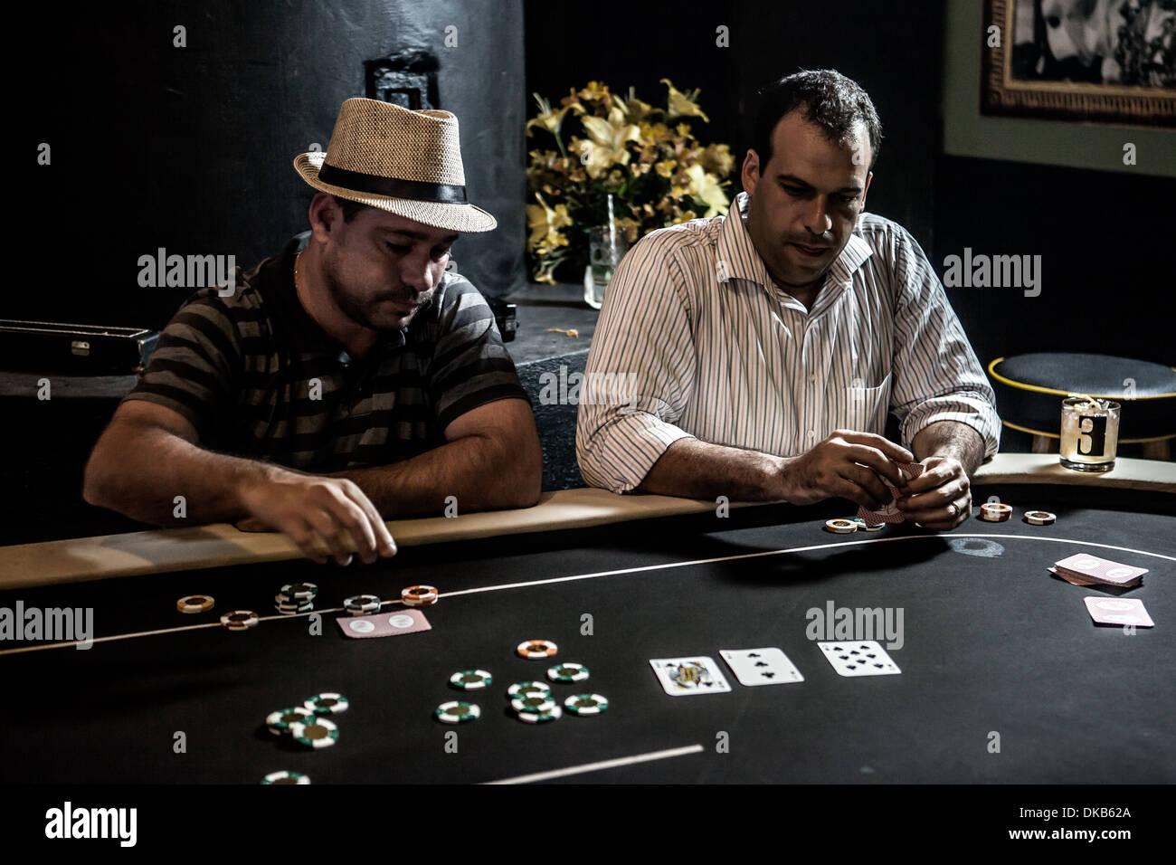 Metà uomini adulti giocando a poker e bere cocktail Immagini Stock
