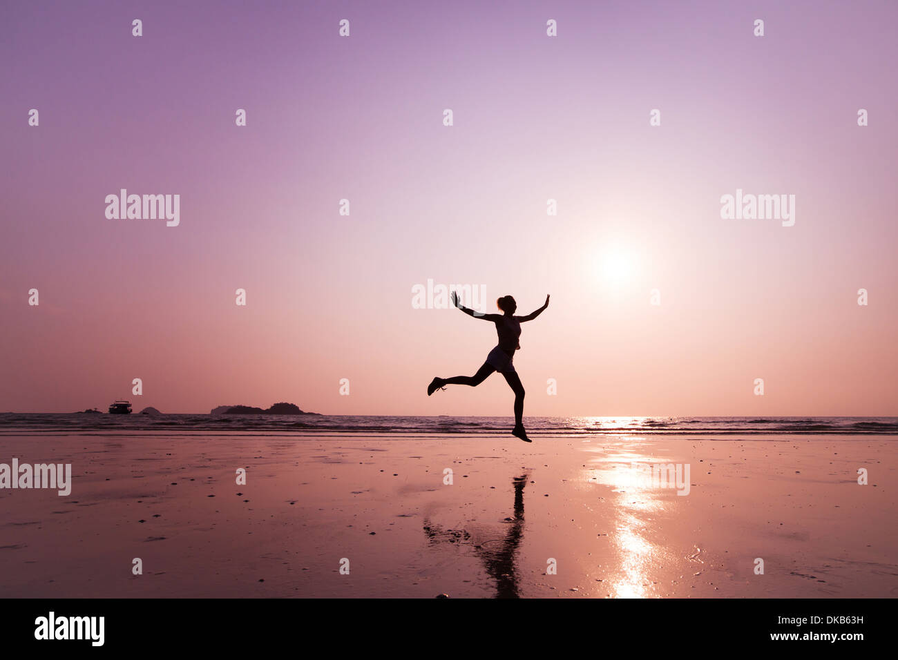 Giovane donna salta sulla spiaggia Immagini Stock