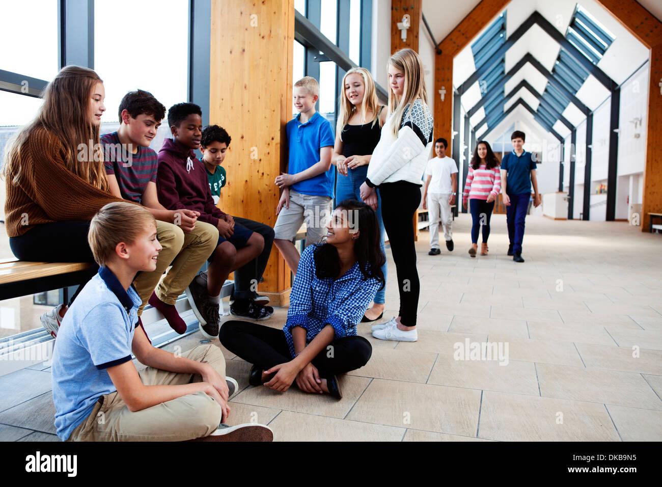 Gruppo di scolari adolescenti seduti chiacchierando in corridoio Immagini Stock