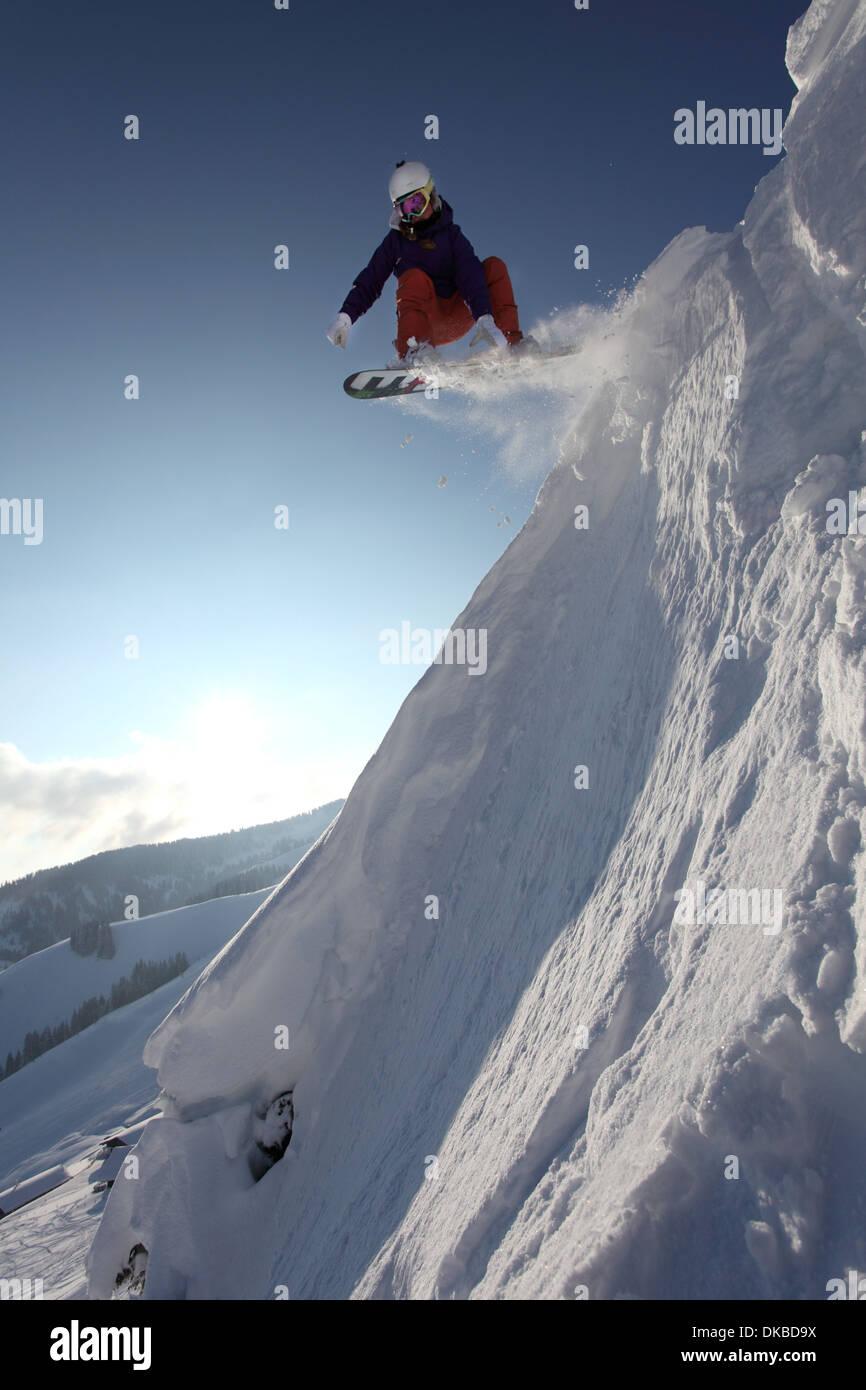 Snowboarder saltare giù la montagna Immagini Stock