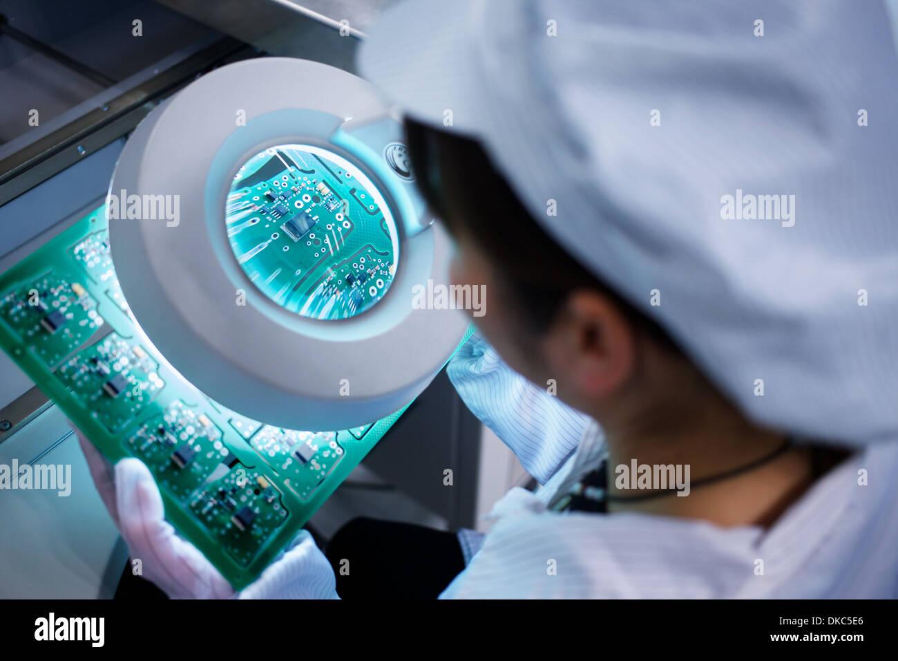 Lavoratore in piccole parti di stabilimento di produzione in Cina cerca attraverso la lente ad microchip Immagini Stock