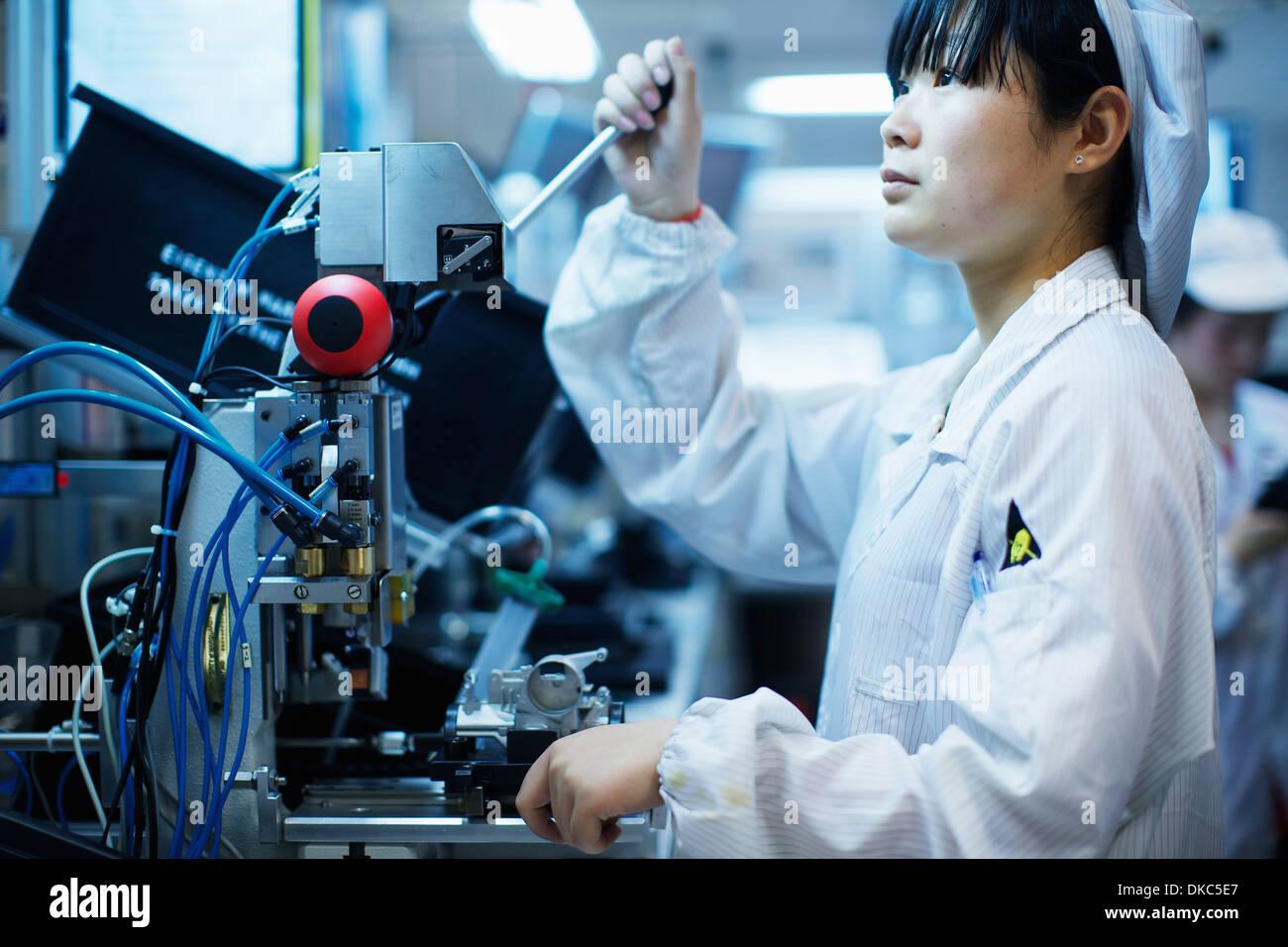 Lavoratore in piccole parti di stabilimento di produzione in Cina Immagini Stock