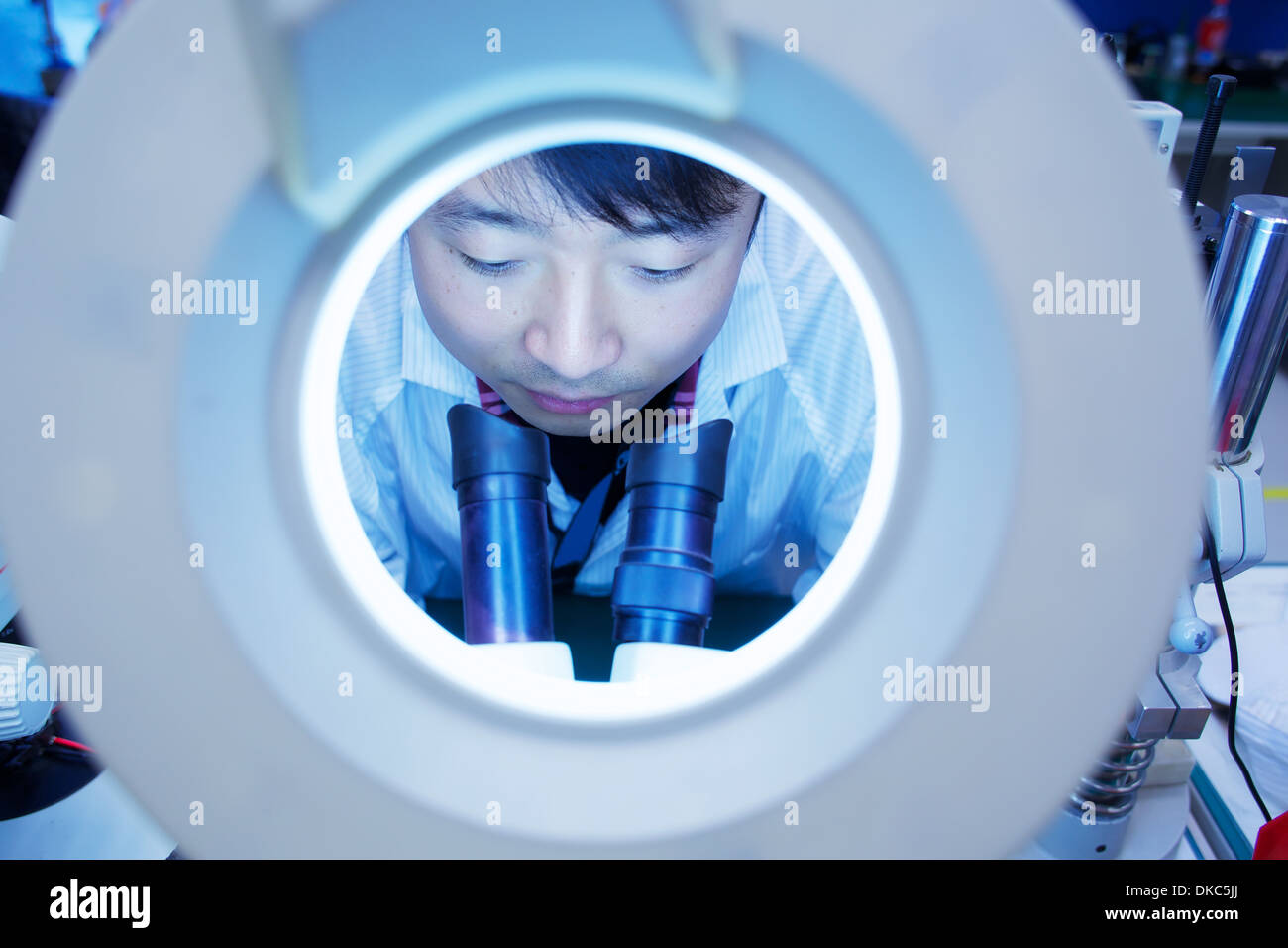 Lavoratore in piccole parti di stabilimento di produzione in Cina guardando attraverso il microscopio Immagini Stock