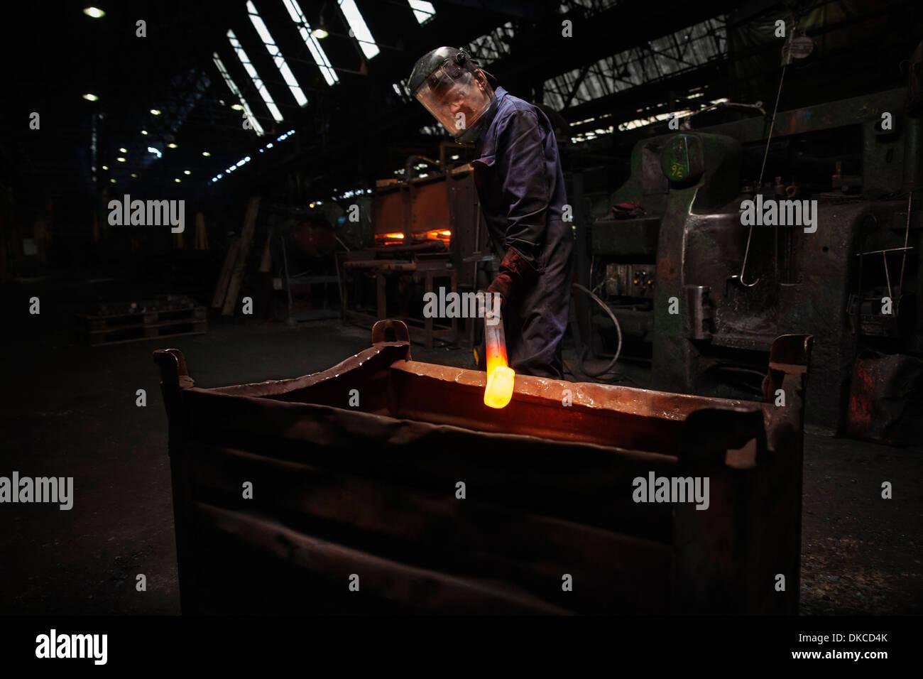 Forge lavoratore preparando a rilasciare finito di sconvolgere la fucinatura in contenitore in acciaio Immagini Stock