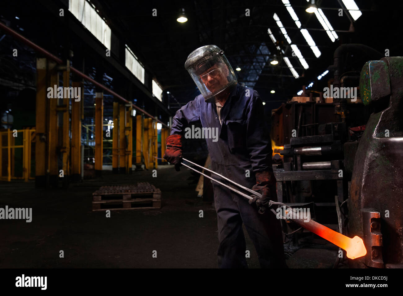 Forge lavoratore con un sconvolto la forgiatura della parte ferroviaria Immagini Stock