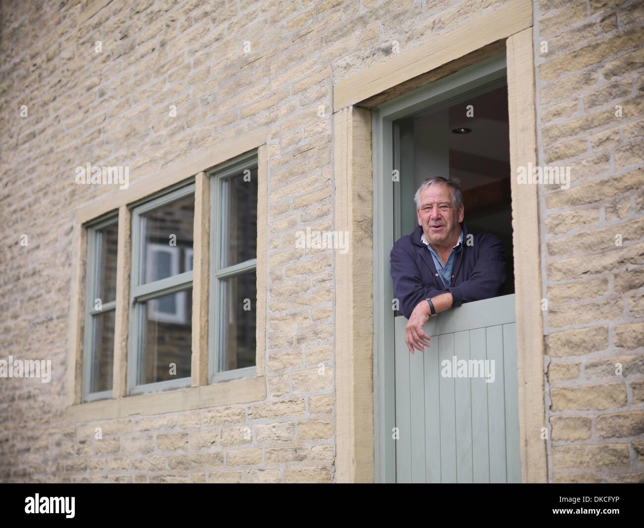 Ritratto di coppia agricoltore guardando fuori dalla porta di casa colonica Immagini Stock