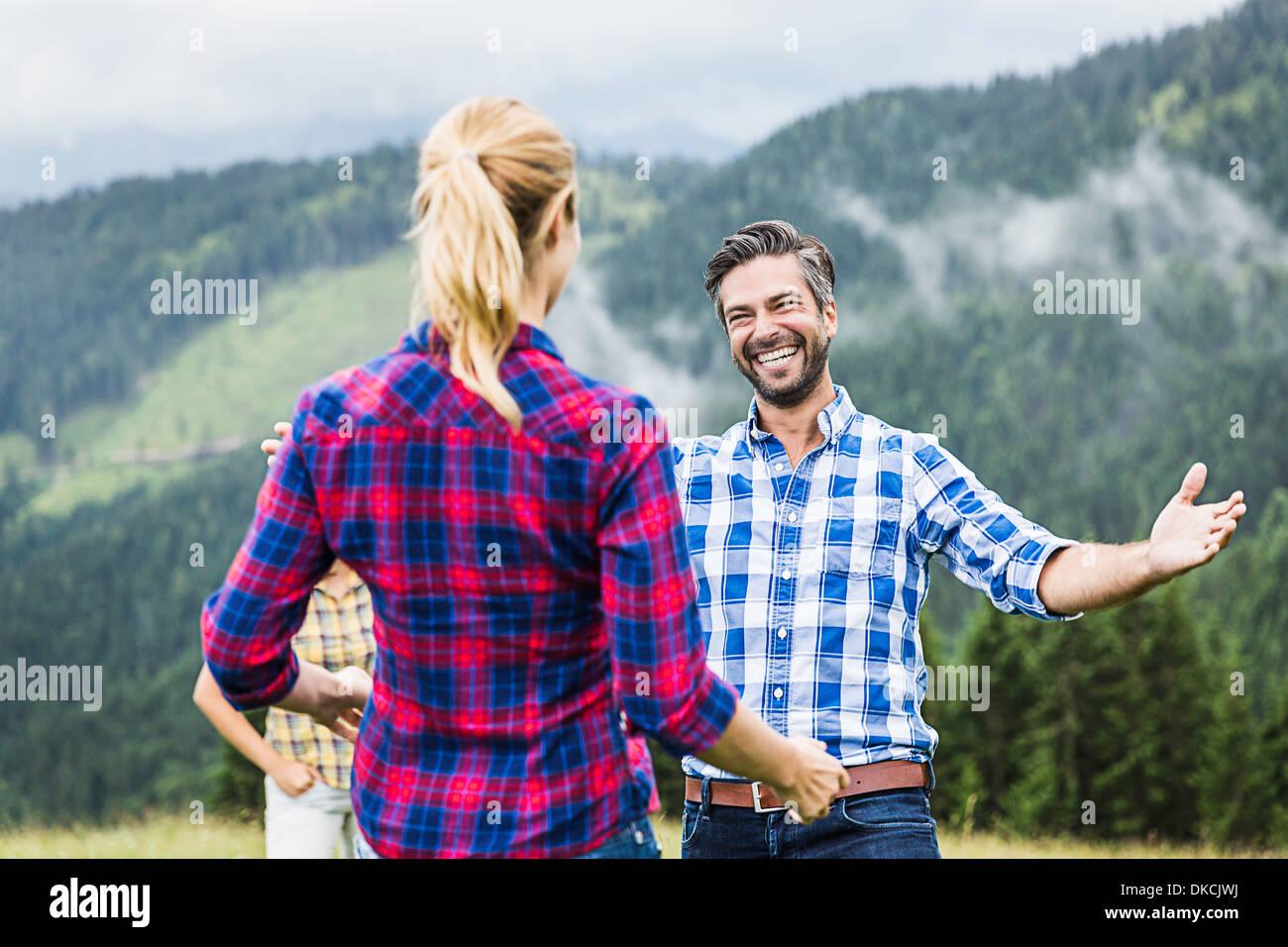Saluto uomo donna con le braccia aperte, Tirolo, Austria Immagini Stock