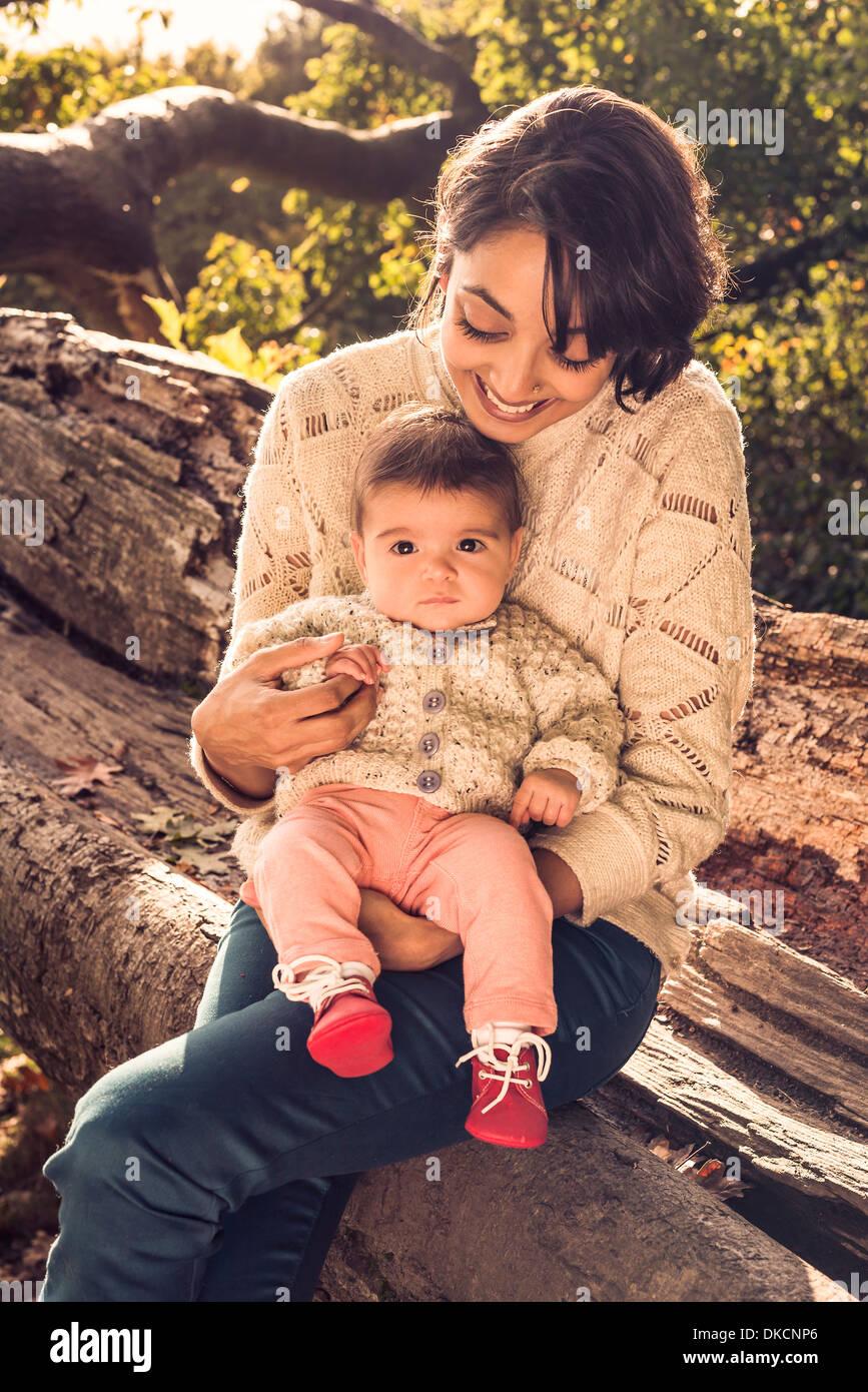 La madre e il bambino seduto sul log Immagini Stock