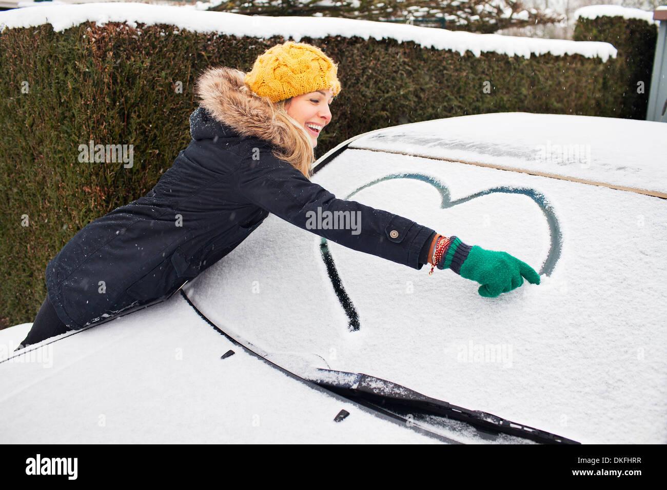 Donna disegno forma di cuore su strade coperte di neve parabrezza Immagini Stock